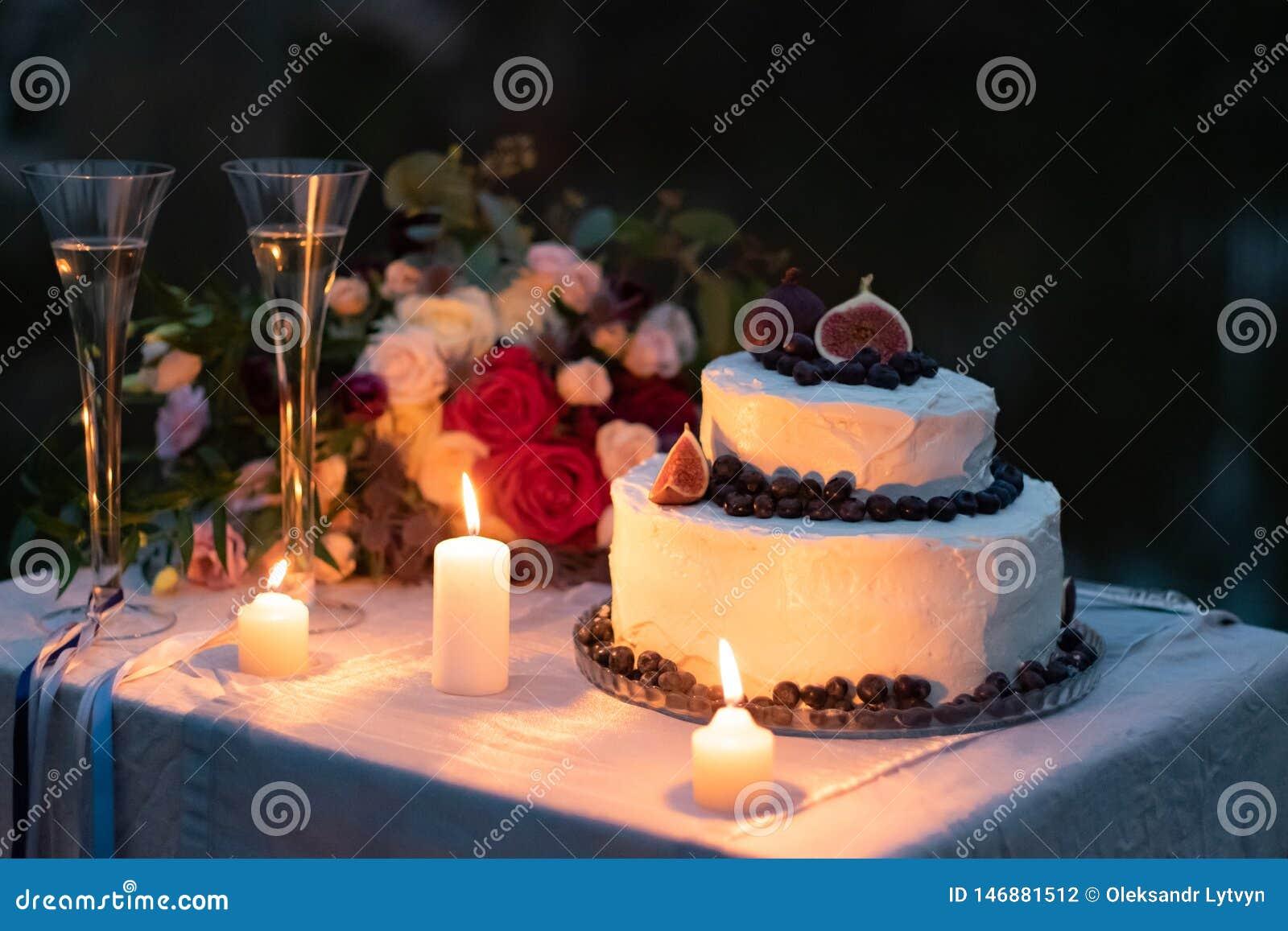 Γαμήλιες διακοσμήσεις κέικ στο άσπρο λούστρο με ένα ντεκόρ των βακκινίων και των σύκων στον πίνακα το βράδυ με τα γυαλιά, αναμμέν