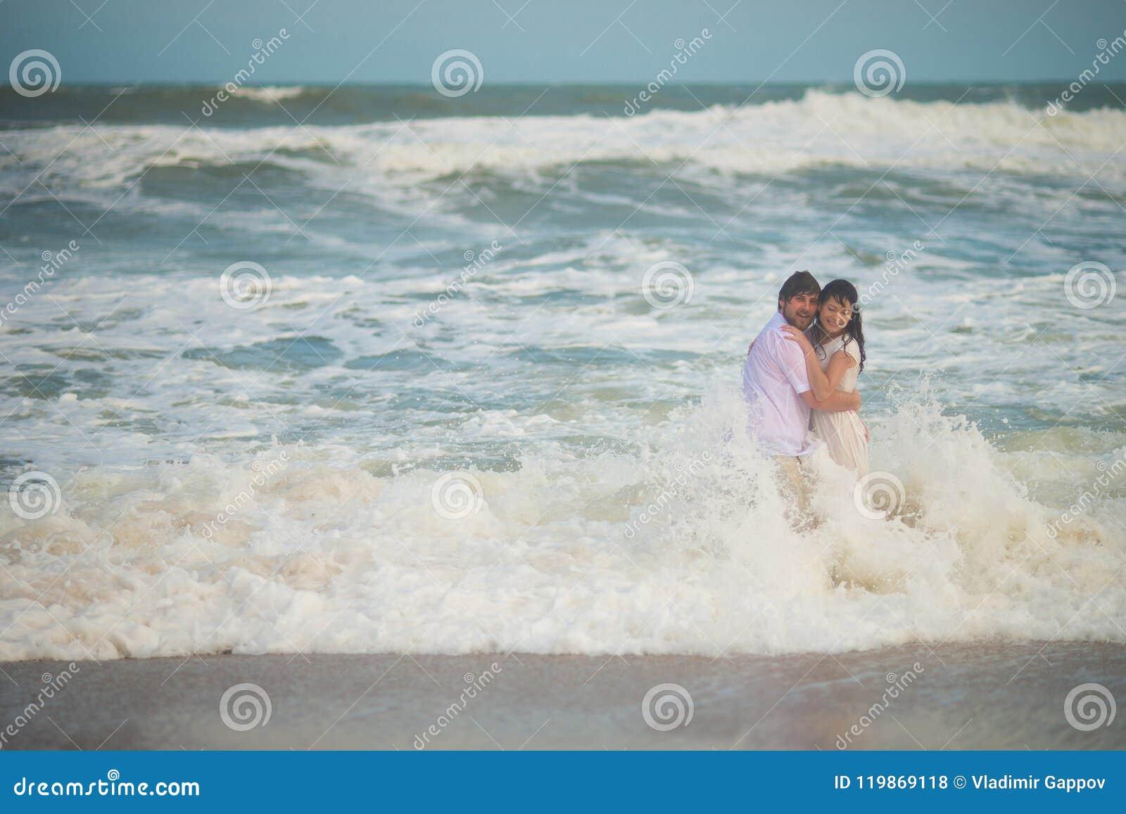 Γαμήλιο ζεύγος που στέκεται υγρό στο θαλάσσιο νερό