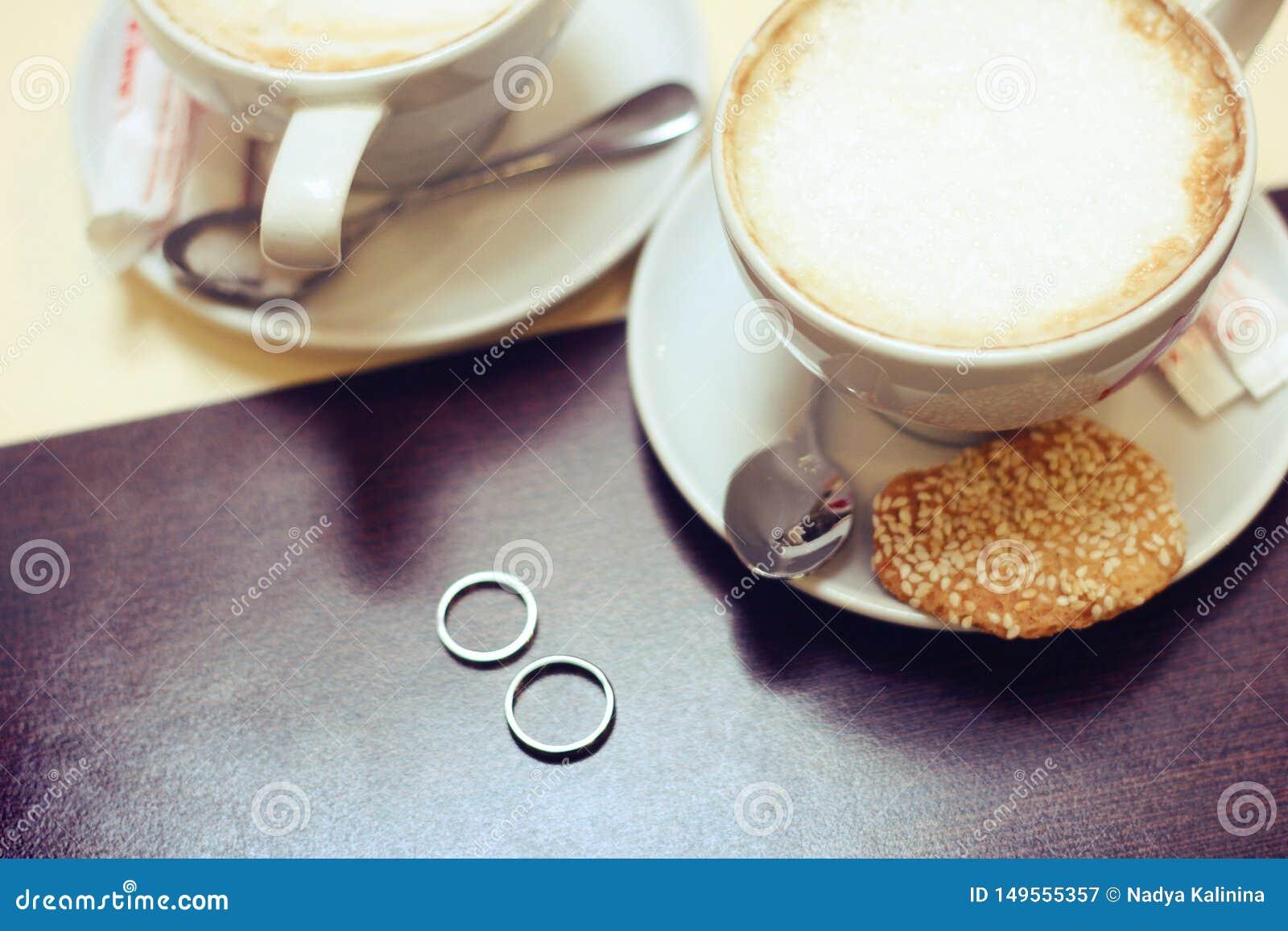Γαμήλιο χρυσό ζεύγος φλιτζανιών του καφέ για τη ρομαντική ημερομηνία εραστών