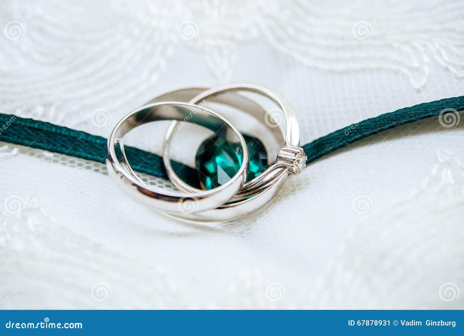 Γαμήλια άσπρος-χρυσά δαχτυλίδια με το διαμάντι και τη σμαραγδένια κορδέλλα