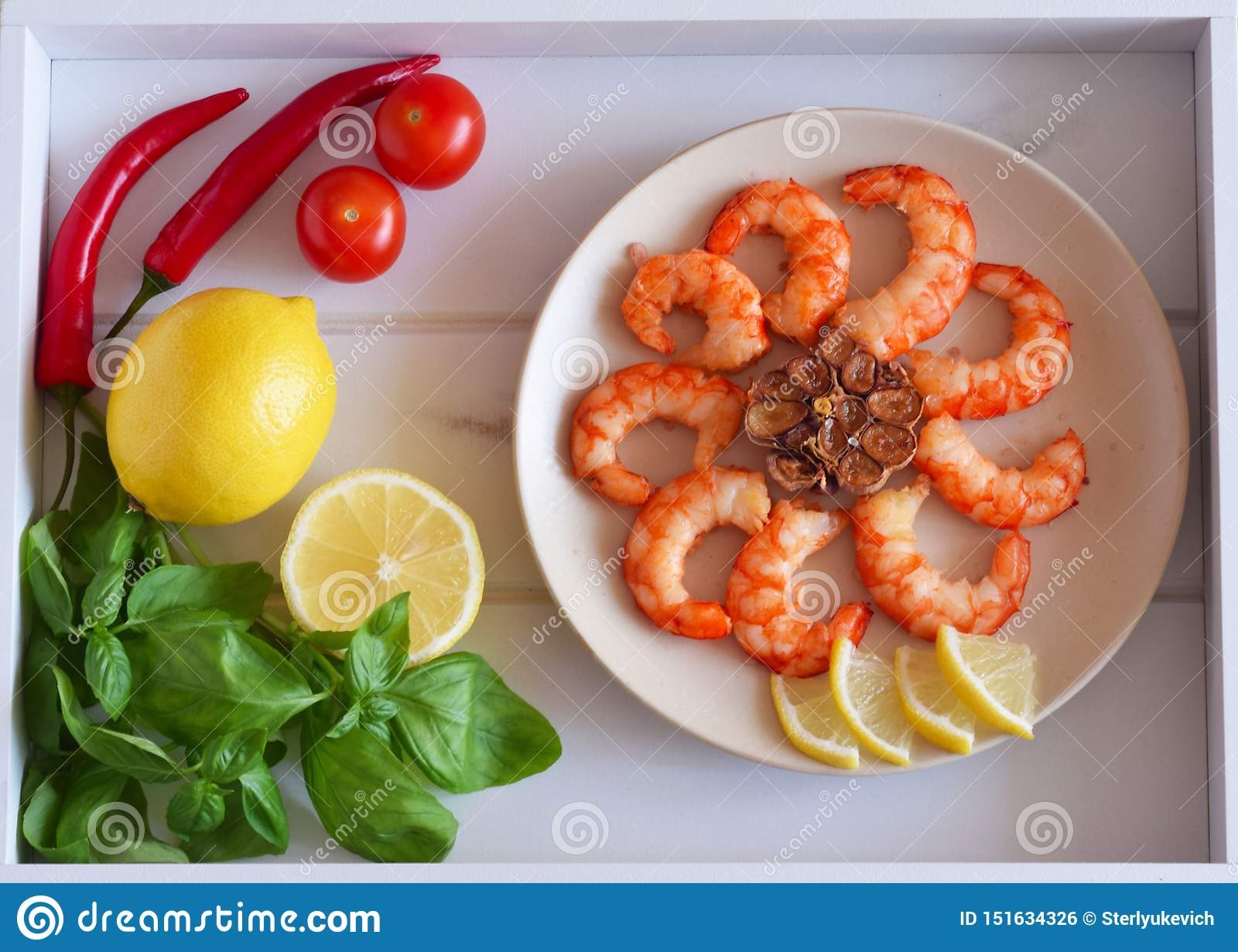 Γαρίδες που τηγανίζονται σε ένα πιάτο και φρέσκα λαχανικά, φρούτα σε έναν όμορφο δίσκο