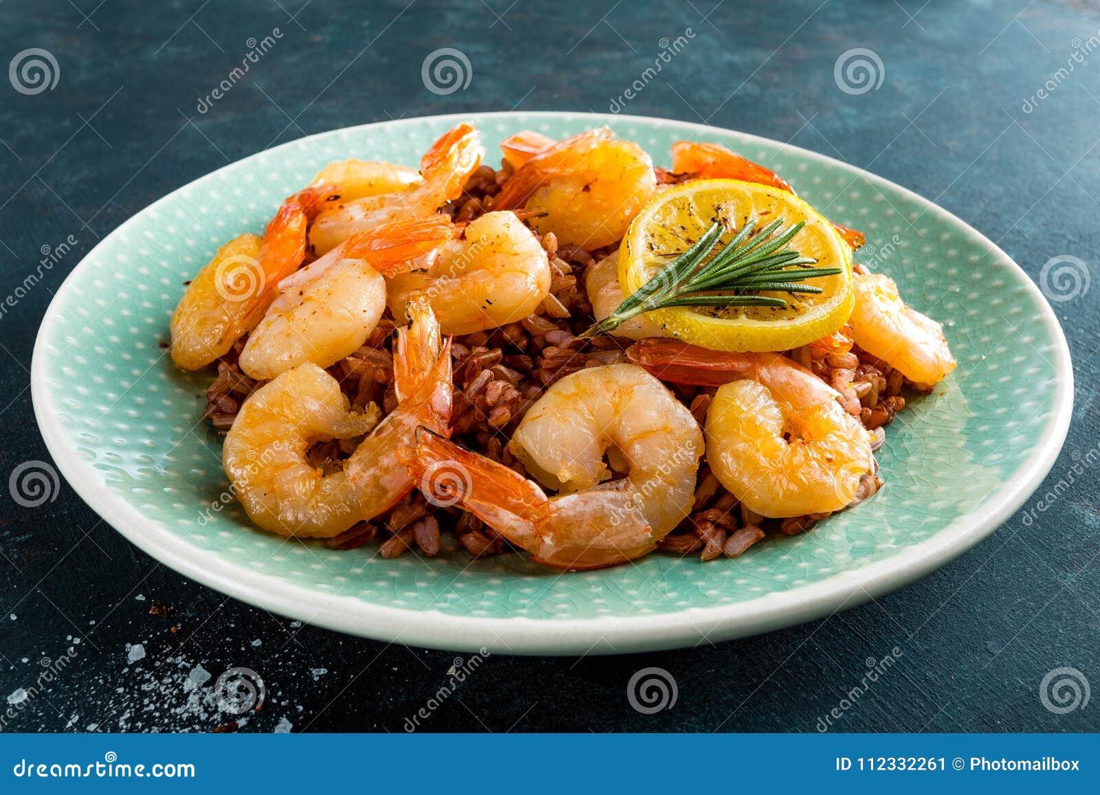 Γαρίδες που ψήνονται στη σχάρα και το βρασμένο καφετί ρύζι στο πιάτο Ψημένες στη σχάρα γαρίδες, γαρίδες με το ρύζι Θαλασσινά ασια