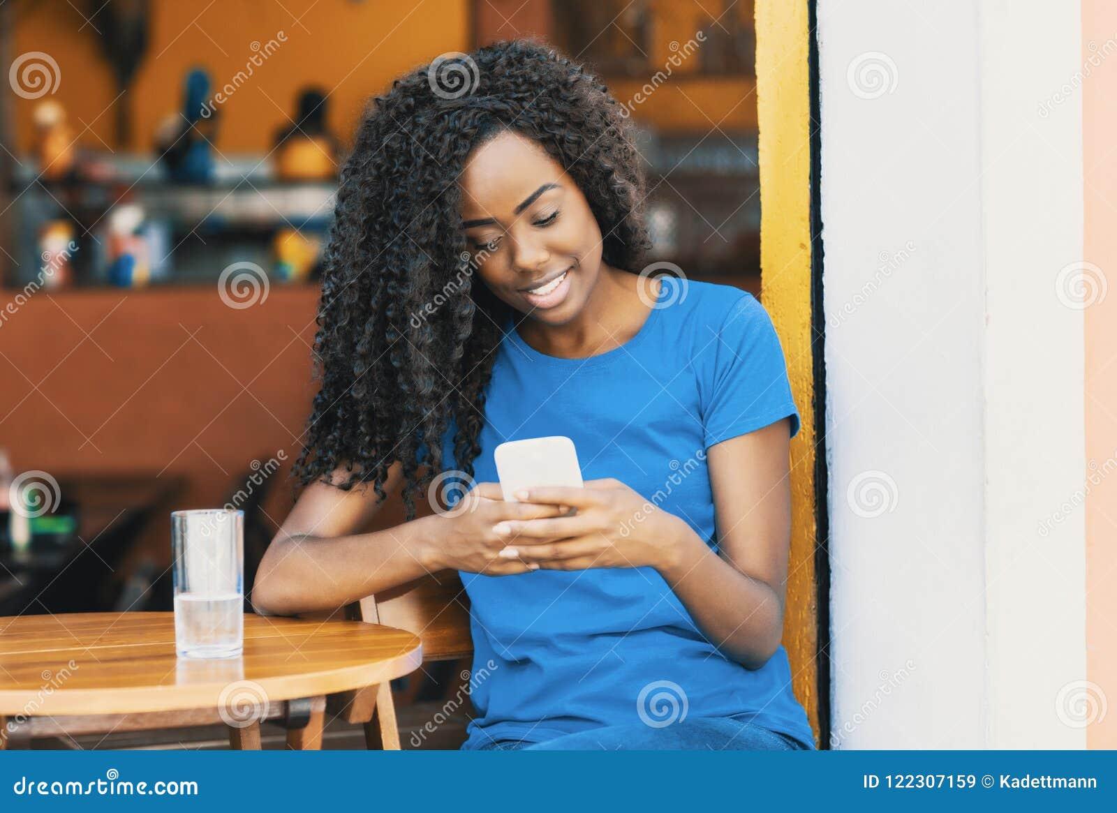 Γελώντας γυναίκα αφροαμερικάνων στο texting μήνυμα φραγμών με το mobi
