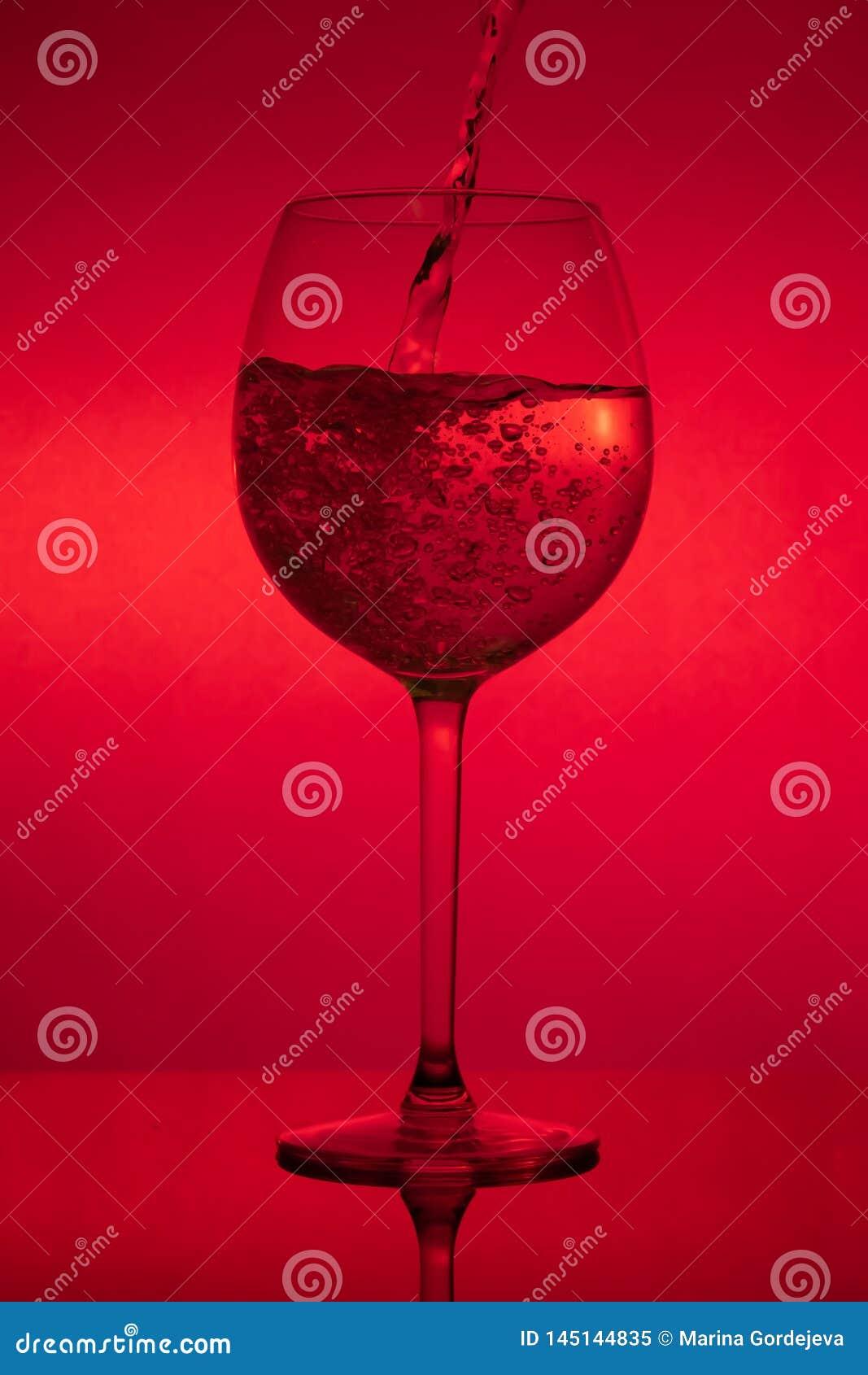 Γεμίζοντας το γυαλί, που χύνει wineglass στο κόκκινο υπόβαθρο
