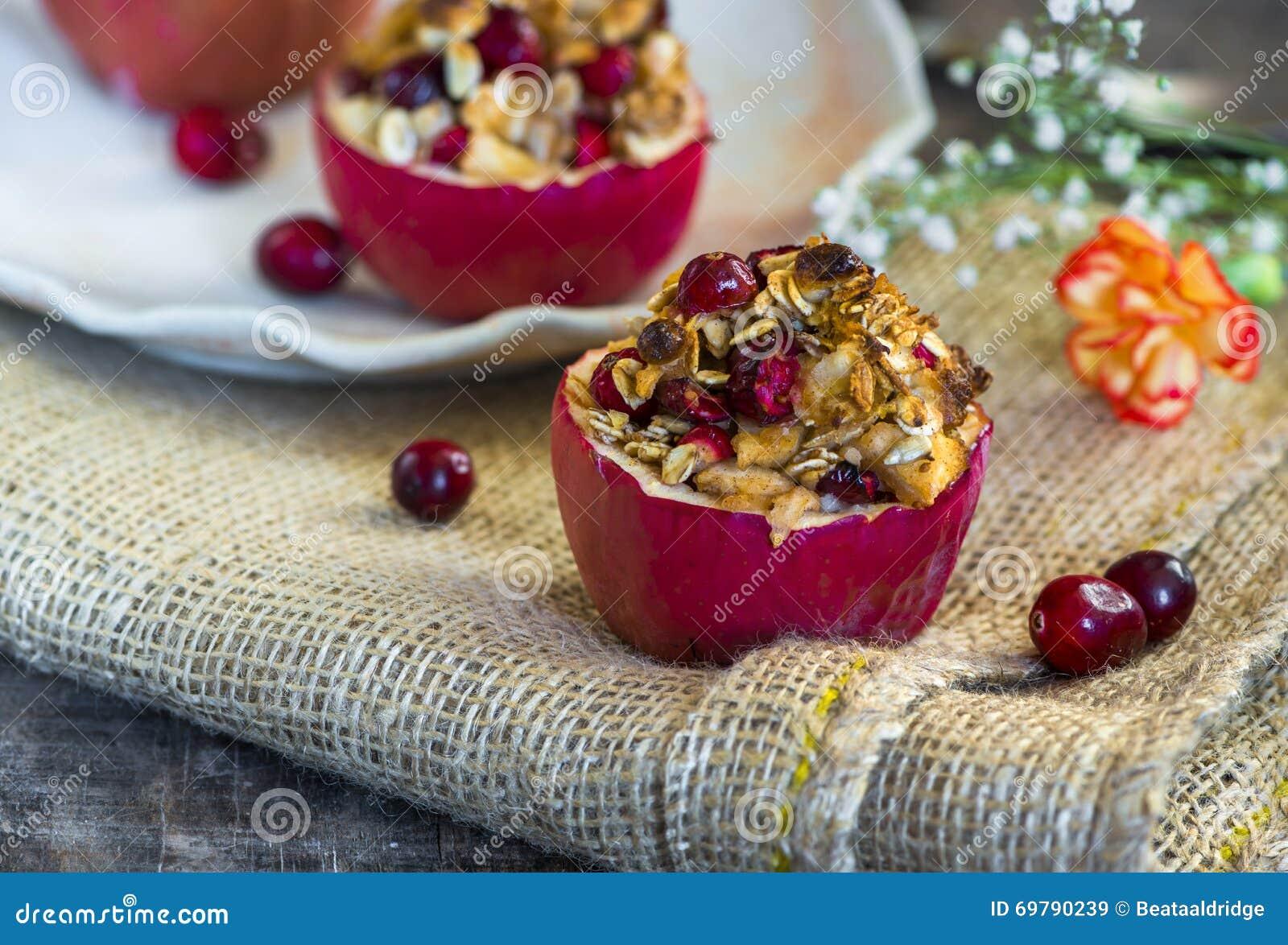 Γεμισμένα ψημένα κόκκινα μήλα με το granola, τα τα βακκίνια και το αμυγδαλωτό