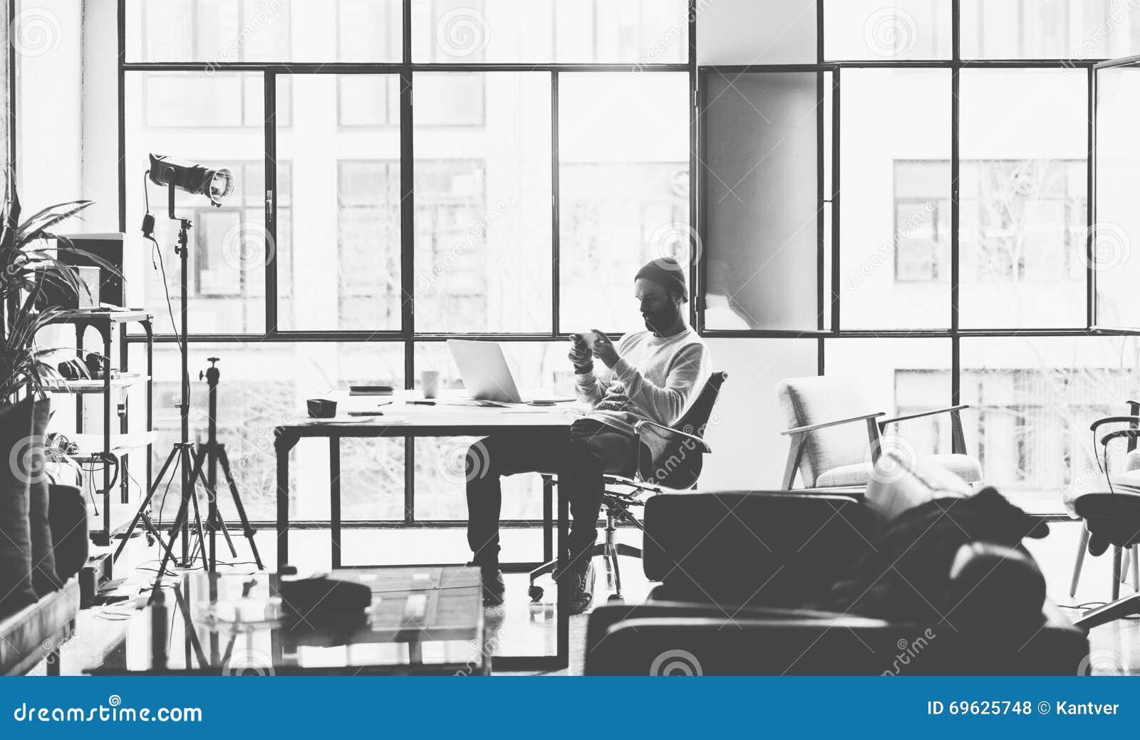 Γενειοφόρος δημιουργικός διευθυντής φωτογραφιών που εργάζεται με το νέο στούντιο σοφιτών ανοιχτού χώρου προγράμματος Σύγχρονο sma
