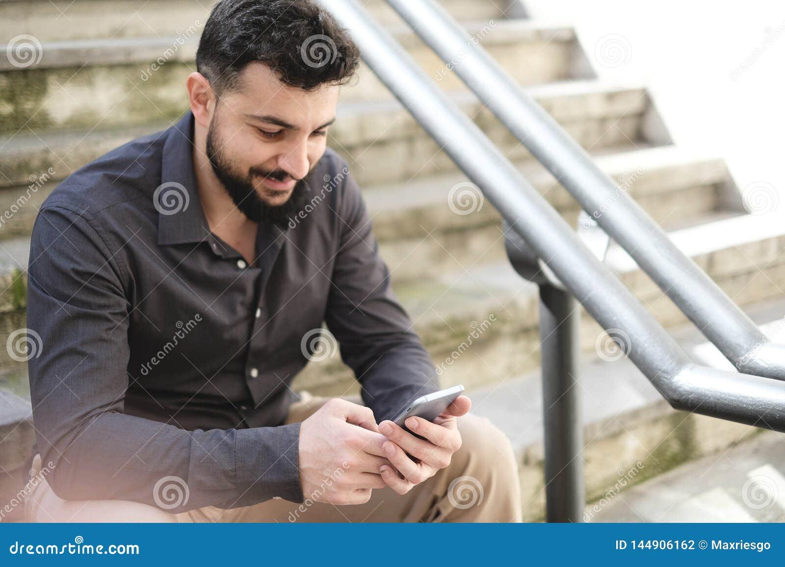 Γενειοφόρο άτομο που φαίνεται smartphone στα σκαλοπάτια