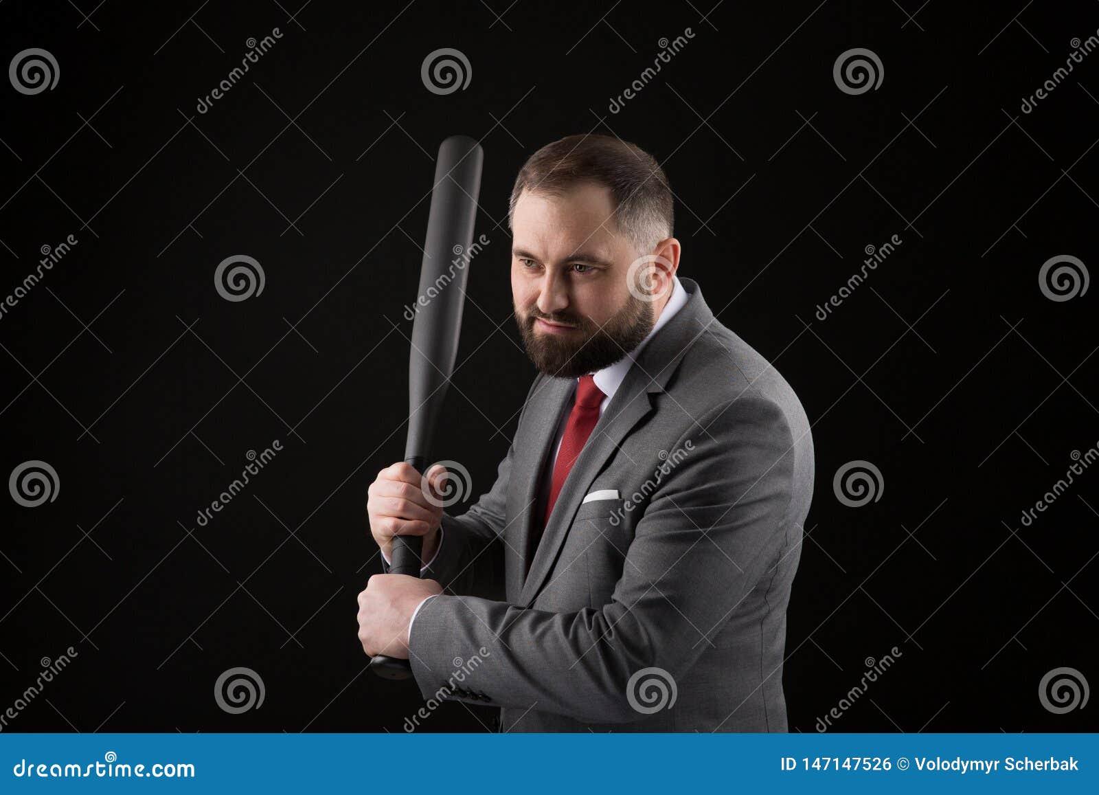 Γενειοφόρο άτομο στο κοστούμι και κόκκινος δεσμός με το ρόπαλο του μπέιζμπολ