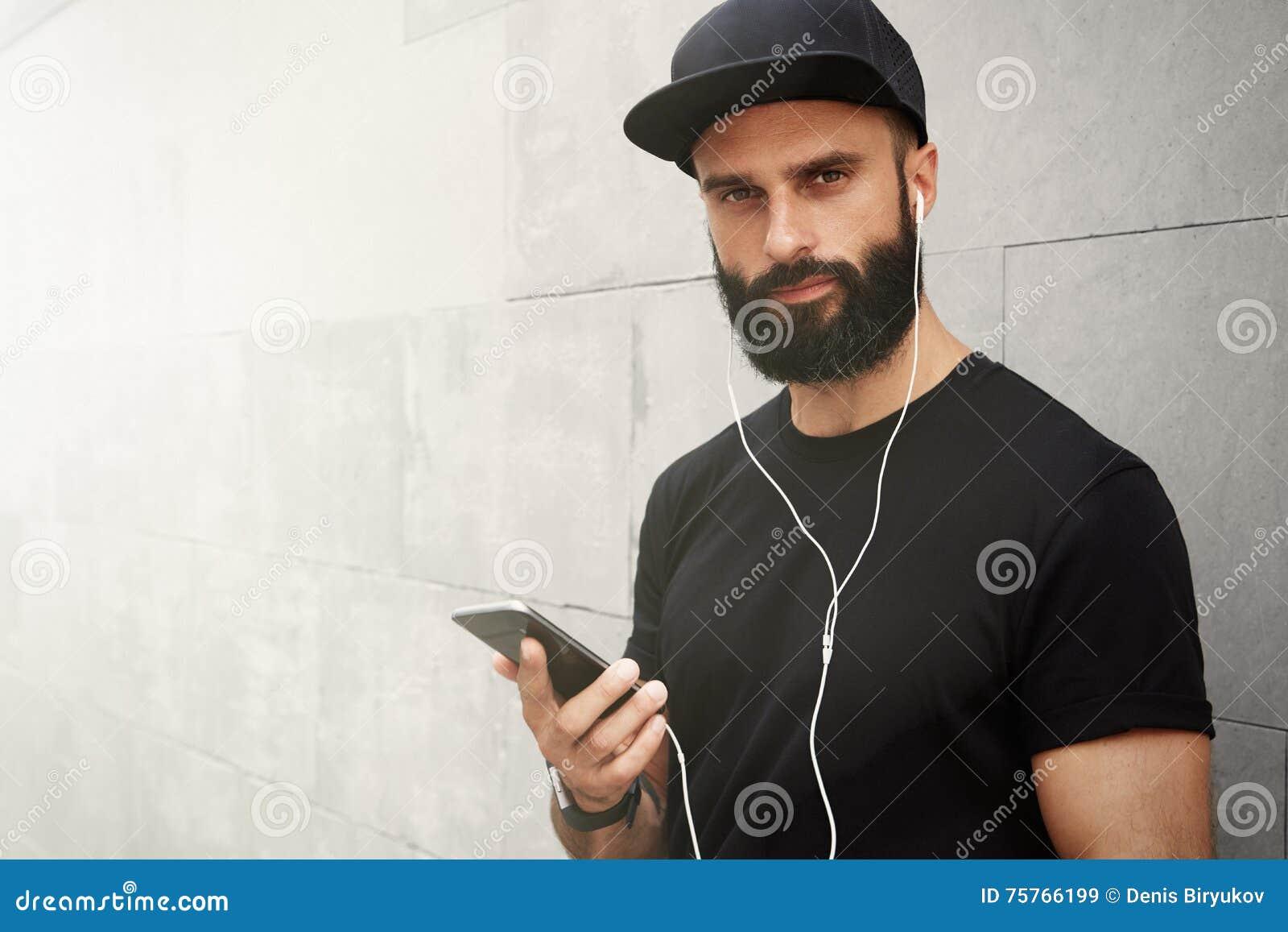 Γενειοφόρο μυϊκό άτομο που φορά το μαύρο θερινό χρόνο Snapback ΚΑΠ μπλουζών κενό Νεαροί άνδρες που χαμογελούν απέναντι από το κεν