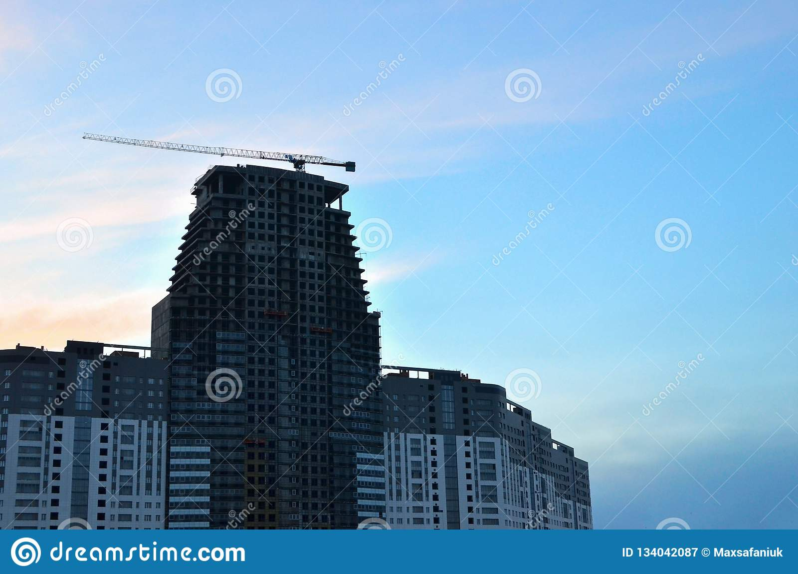 Γερανός και εργοτάξιο οικοδομής οικοδόμησης ενάντια στο μπλε ουρανό με τον κενό άσπρο πίνακα διαφημίσεων για τη διαφήμιση στην κο