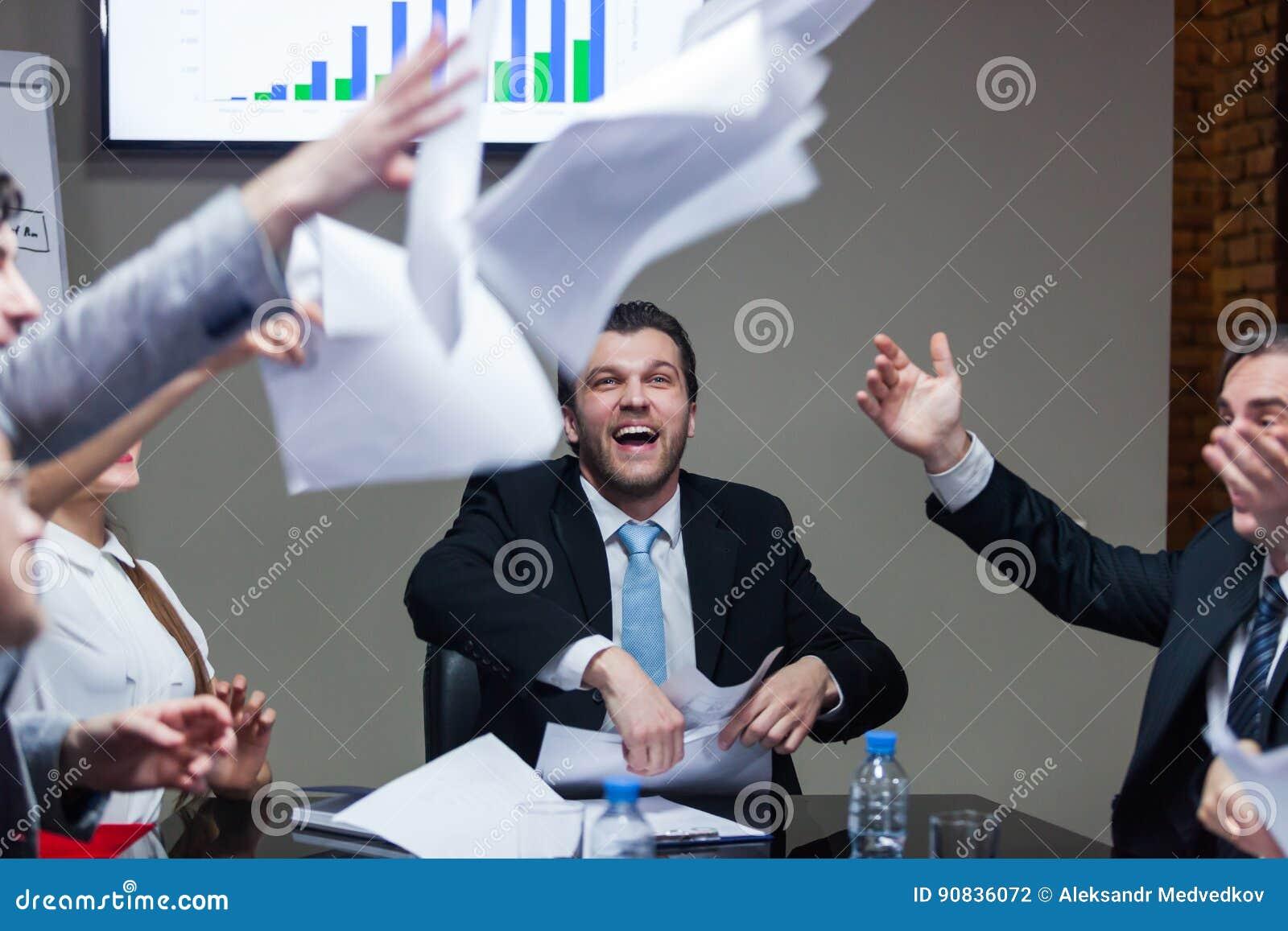 Γελώντας άνθρωποι στον πίνακα που ρίχνουν τα έγγραφα