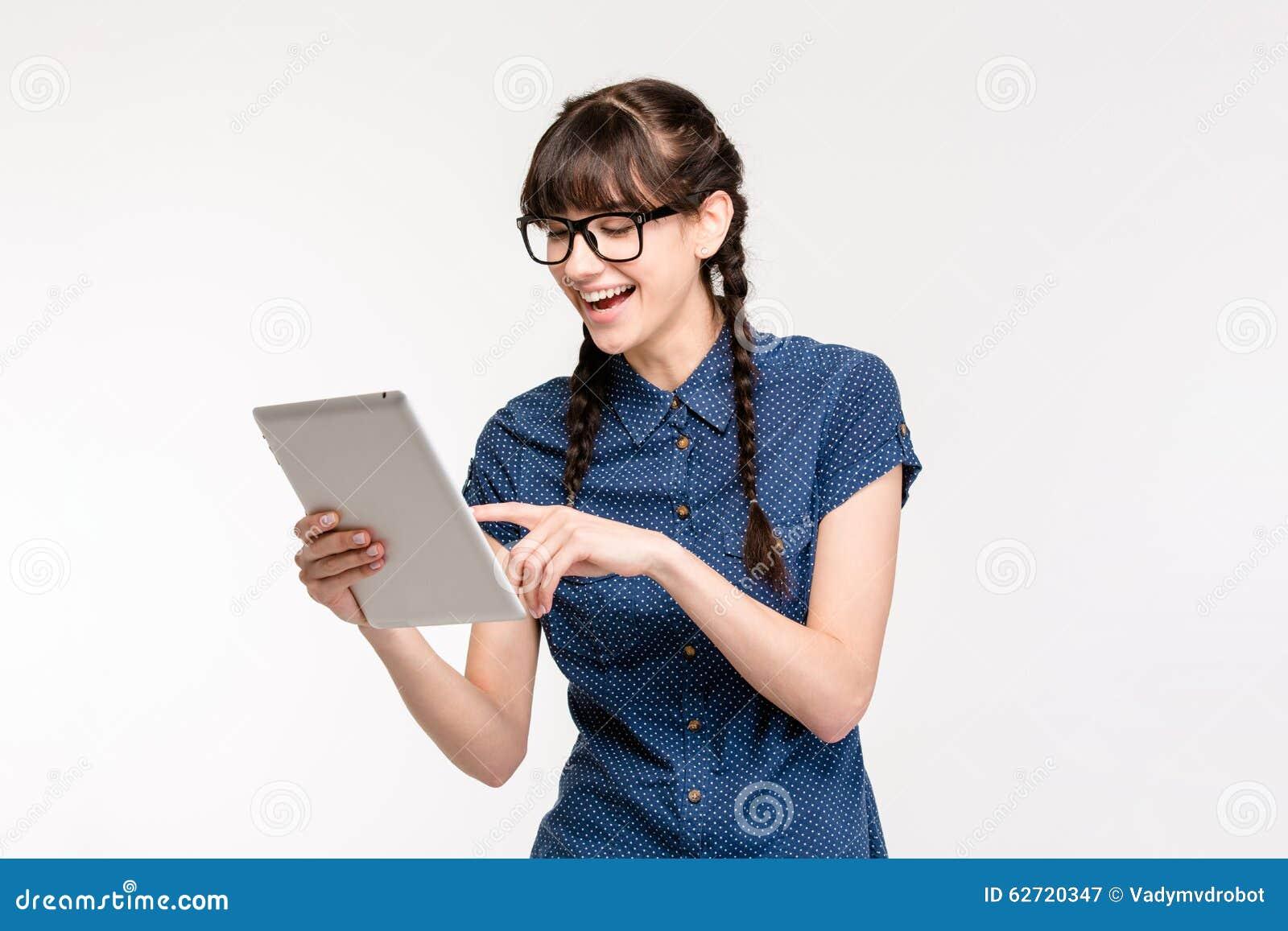 Γελώντας θηλυκός έφηβος που χρησιμοποιεί τον υπολογιστή ταμπλετών