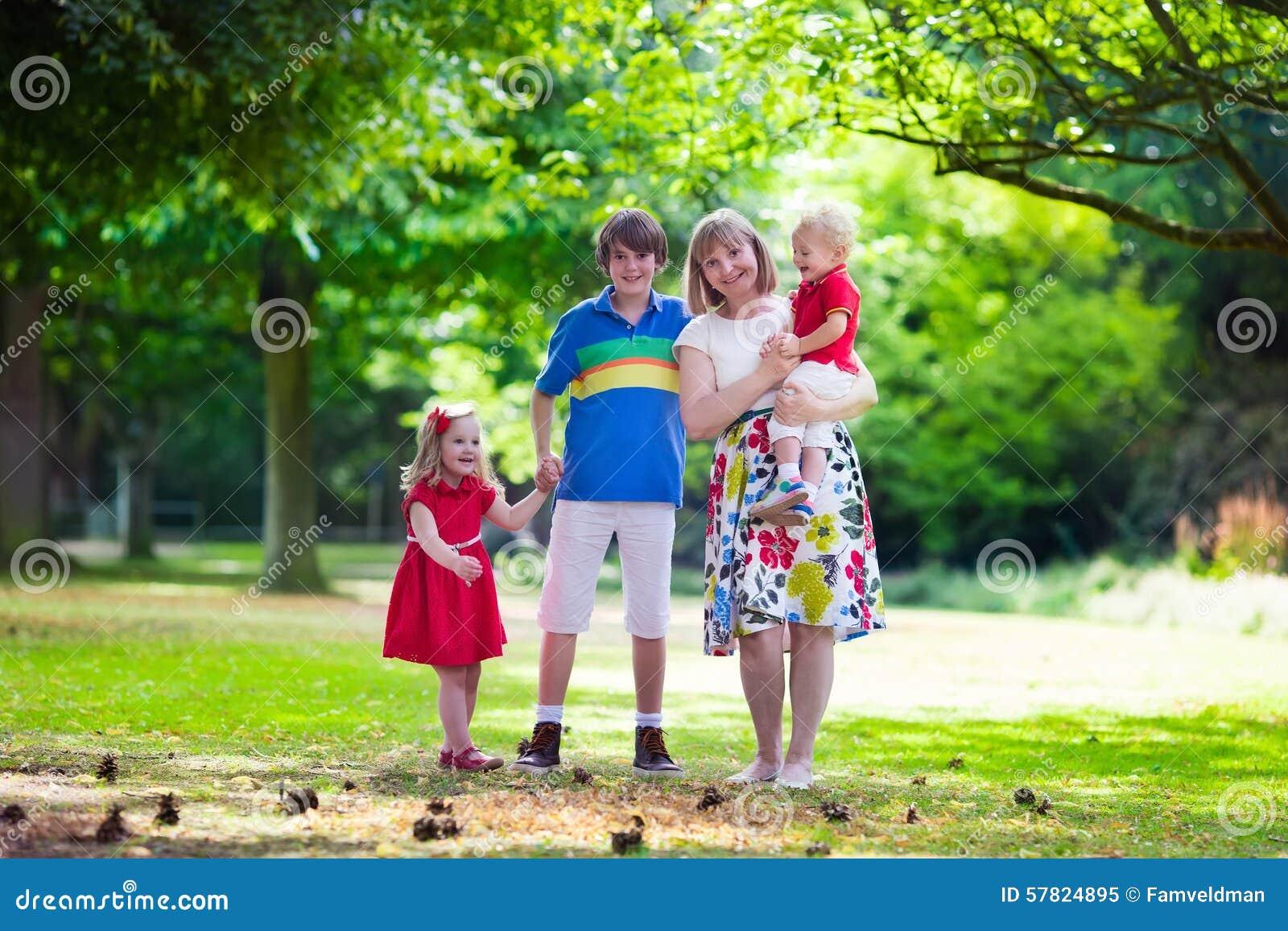 8644ec26703 Download Γιαγιά και παιδιά που περπατούν σε ένα πάρκο Στοκ Εικόνα - εικόνα  από grandparent,