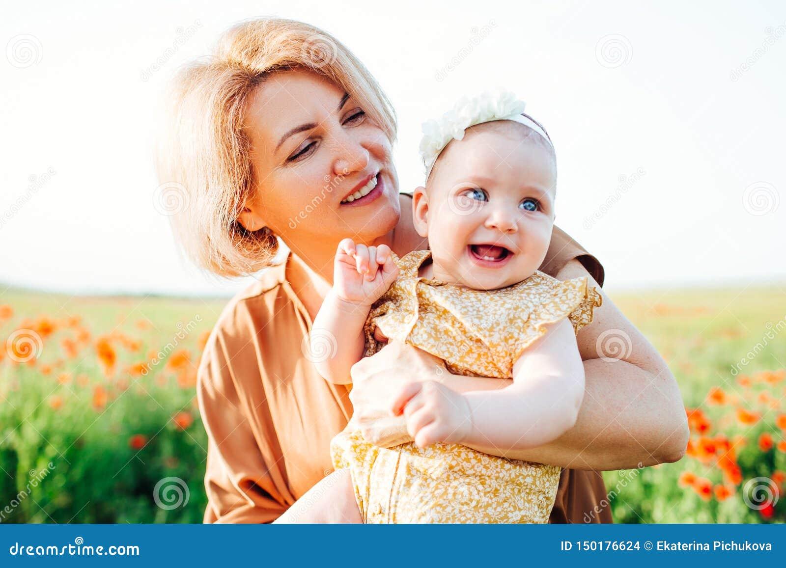 Γιαγιά με μια μικρή εγγονή που παίζει σε έναν τομέα παπαρουνών