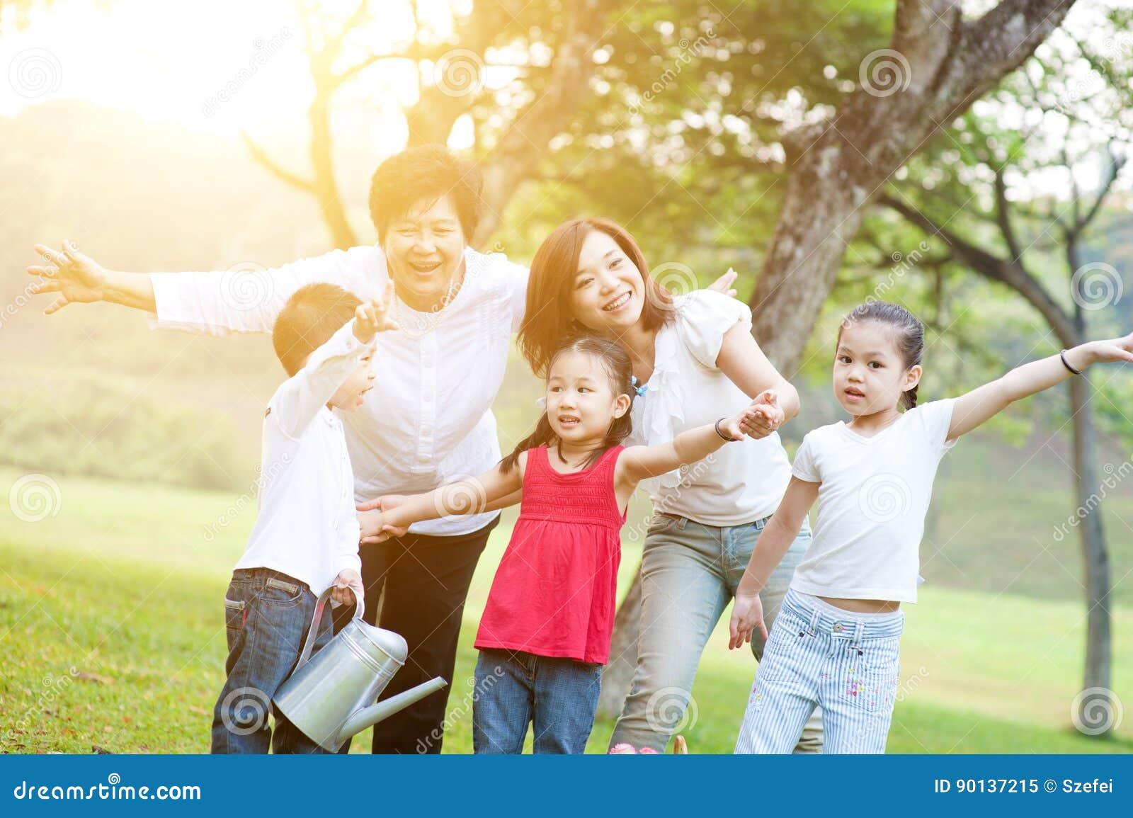 66642abccbe Ειλικρινές πορτρέτο της ευτυχούς πολυ ασιατικής οικογένειας γενεών στο πάρκο  φύσης Υπαίθρια διασκέδαση γιαγιάδων, μητέρων και εγγονιών Υπόβαθρο φλογών  ήλιων ...