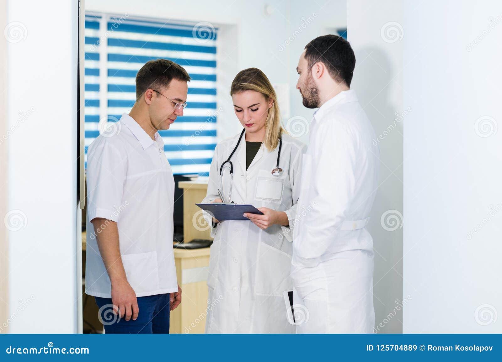 Γιατροί που εργάζονται στο νοσοκομείο και που συζητούν πέρα από τις ιατρικές εκθέσεις Ιατρικό προσωπικό που αναλύει και που εργάζ