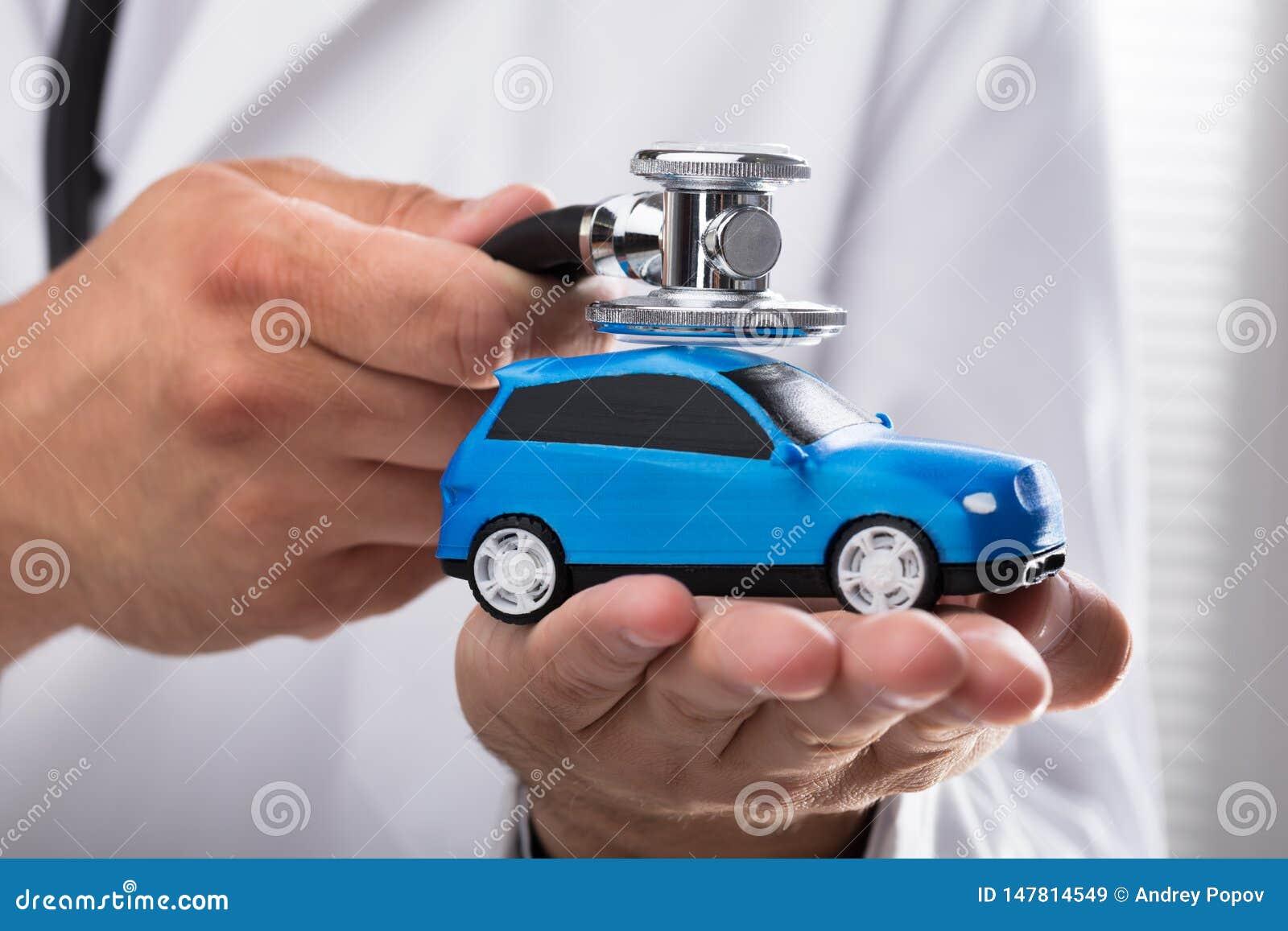 Γιατρός που εξετάζει το μπλε αυτοκίνητο