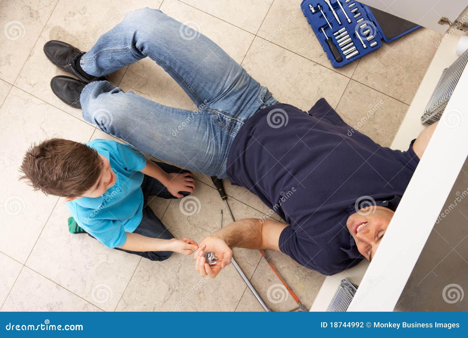 Γιος που βοηθά τον πατέρα για να επιδιορθώσει την καταβόθρα