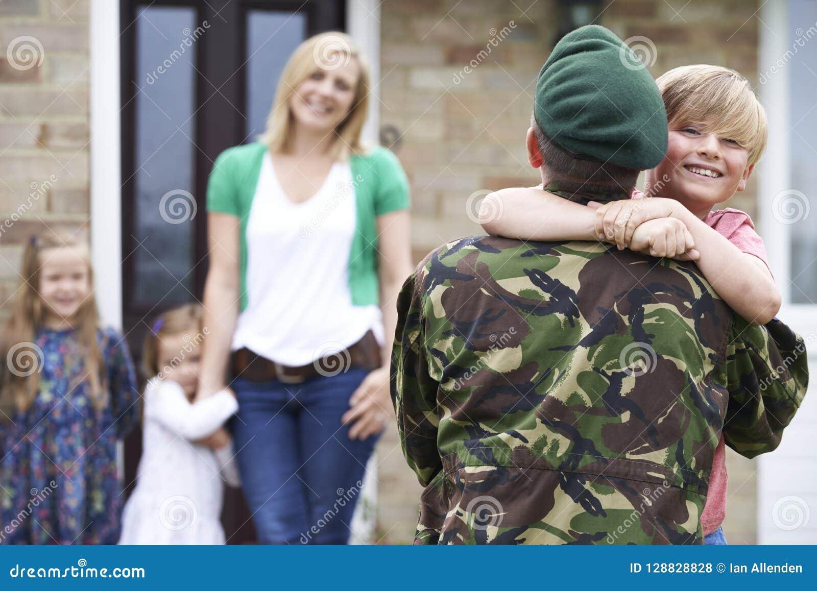 Γιος που χαιρετά το στρατιωτικό πατέρα στην άδεια στο σπίτι