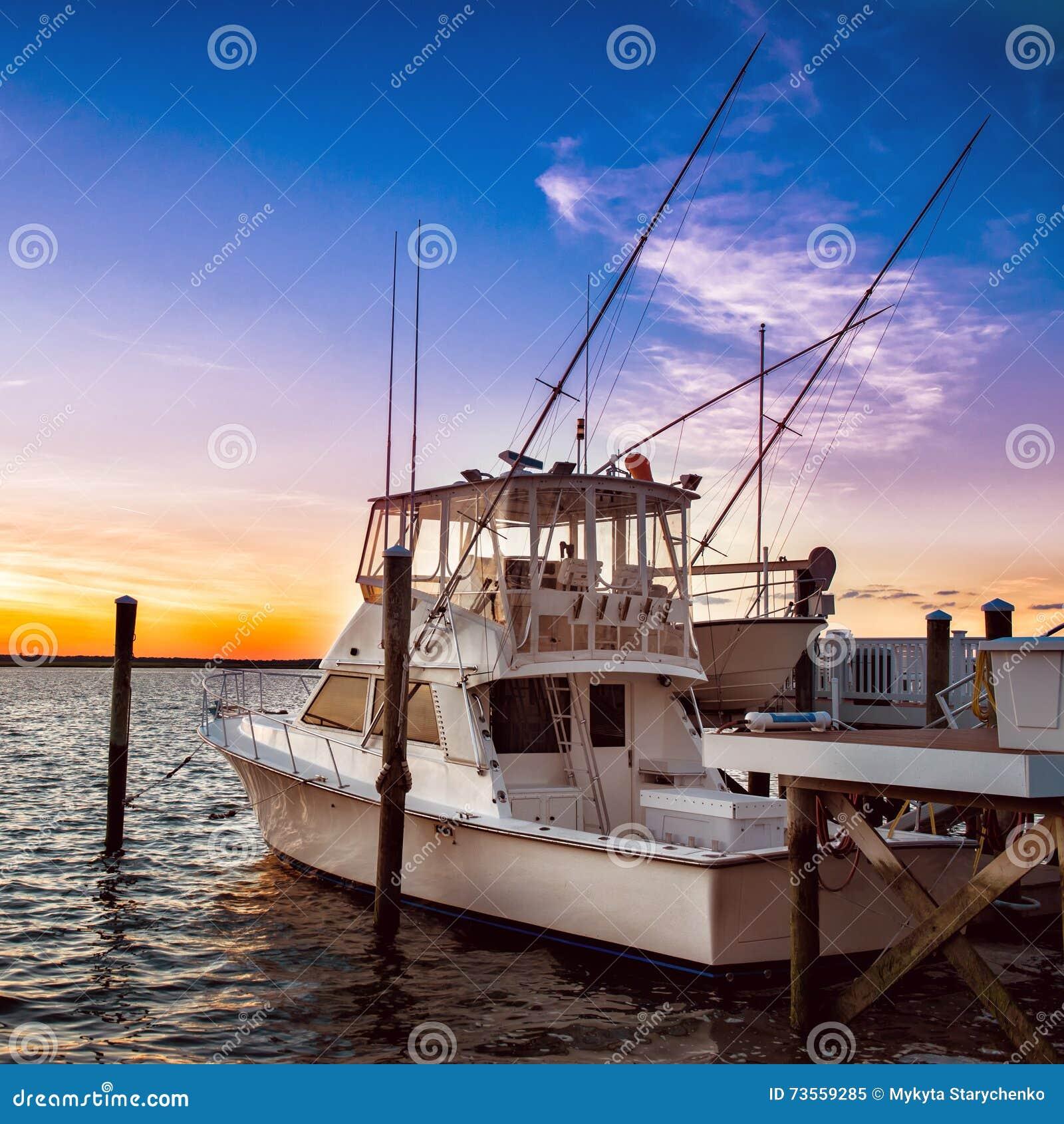 Γιοτ αλιευτικών σκαφών στην αποβάθρα στο ηλιοβασίλεμα στην αποβάθρα λιμνών