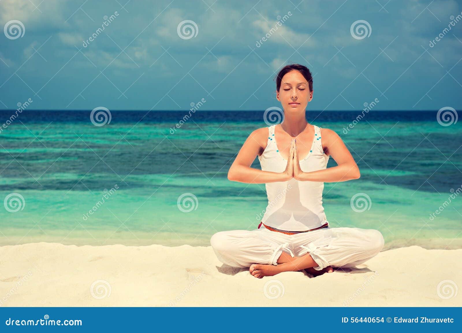 Γιόγκα άσκησης γυναικών στην ακτή