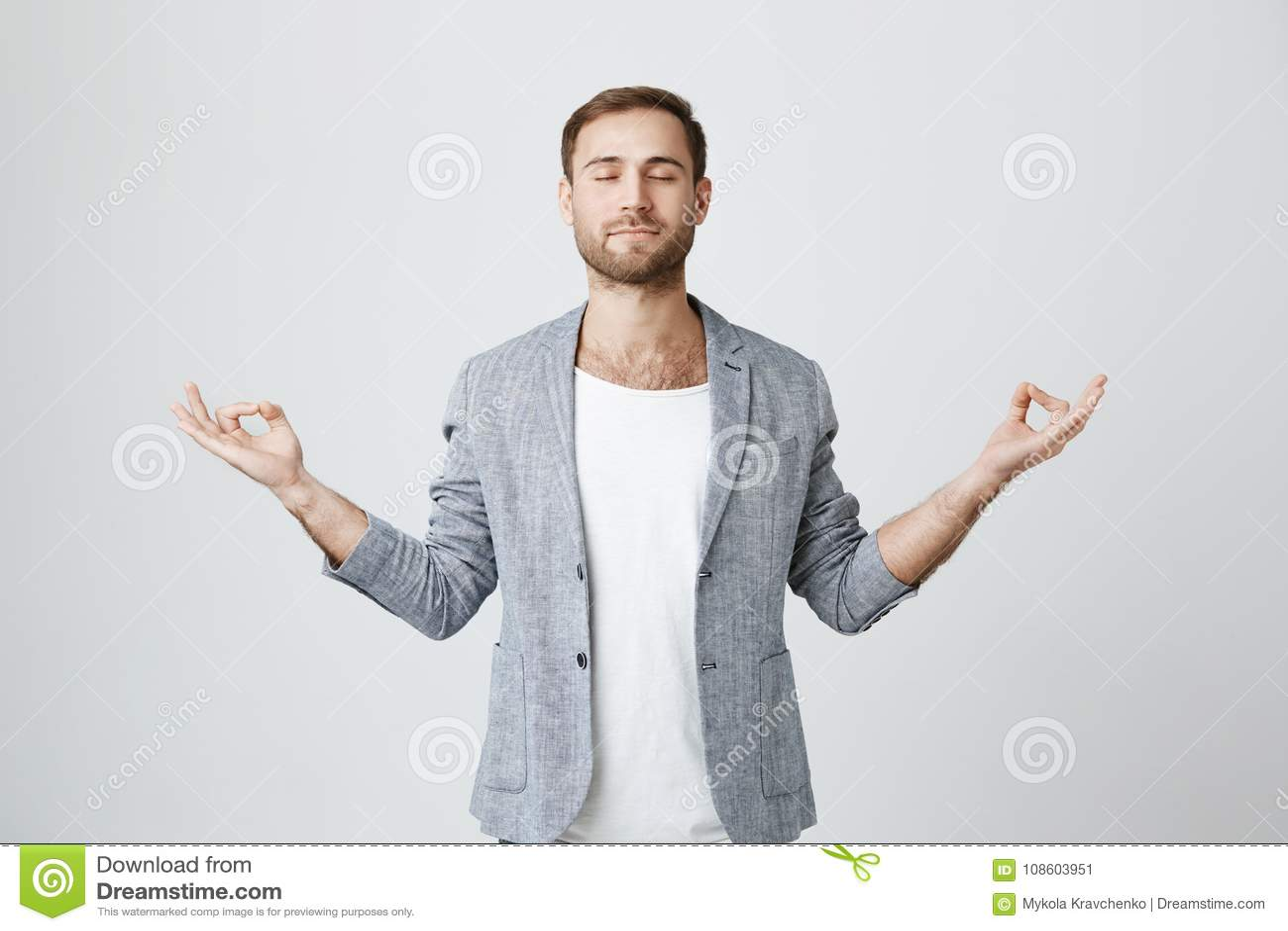 Γιόγκα και περισυλλογή Το όμορφο άτομο με τη γενειάδα έντυσε στο σακάκι που κρατά τις προσοχές ιδιαίτερες meditating, αίσθημα χαλ