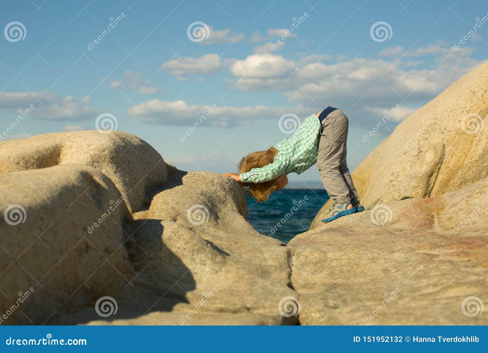 Γιόγκα Γιόγκα παιδιών Αθλητισμός που εκπαιδεύει για τα παιδιά στη φύση Θάλασσα και αθλητισμός Άσπρες πέτρες στην ακτή Χαριτωμένο