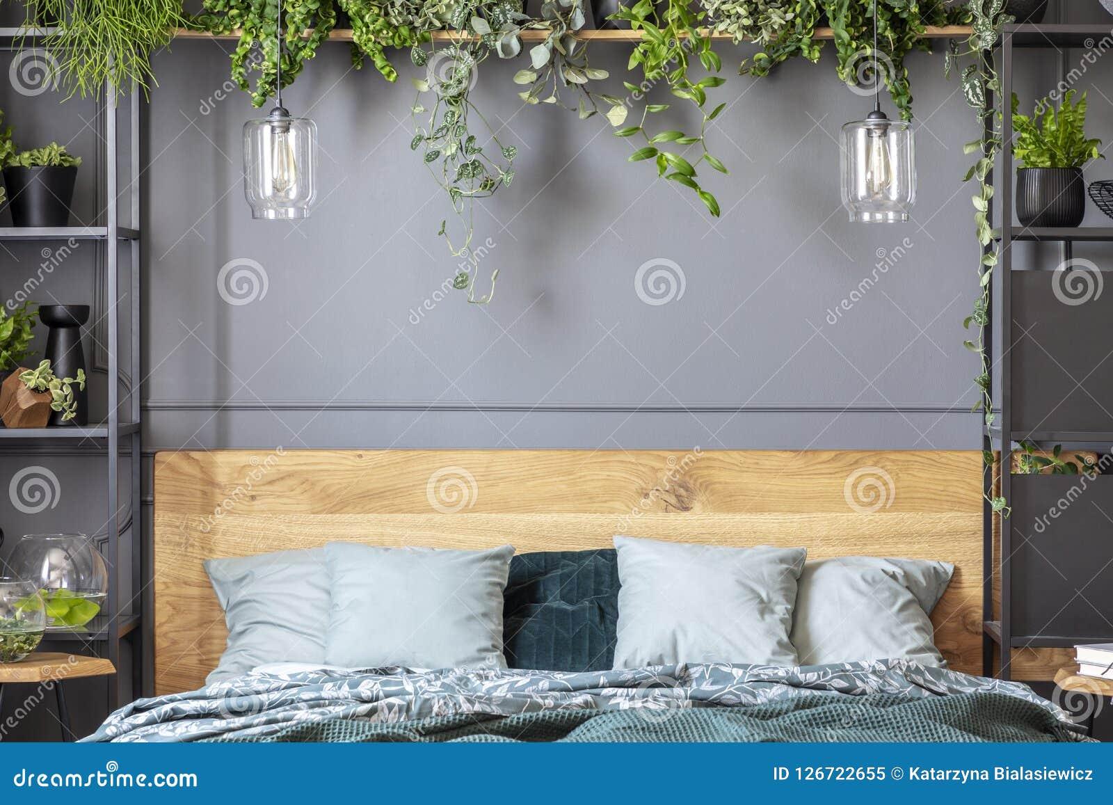 Γκρίζα μαξιλάρια στο κρεβάτι με ξύλινο headboard στα εσωτερικά WI κρεβατοκάμαρων