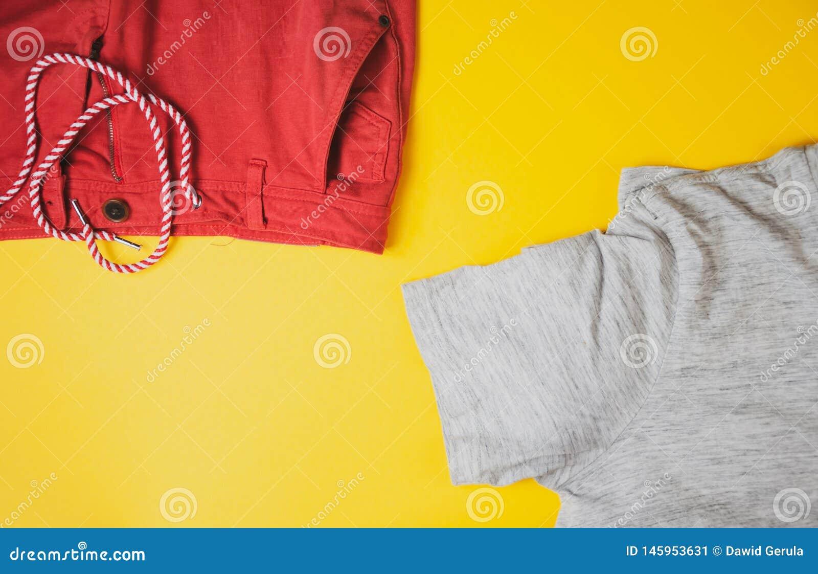 Γκρίζα μπλούζα και κόκκινα σορτς στο κίτρινο υπόβαθρο, άποψη από την κορυφή