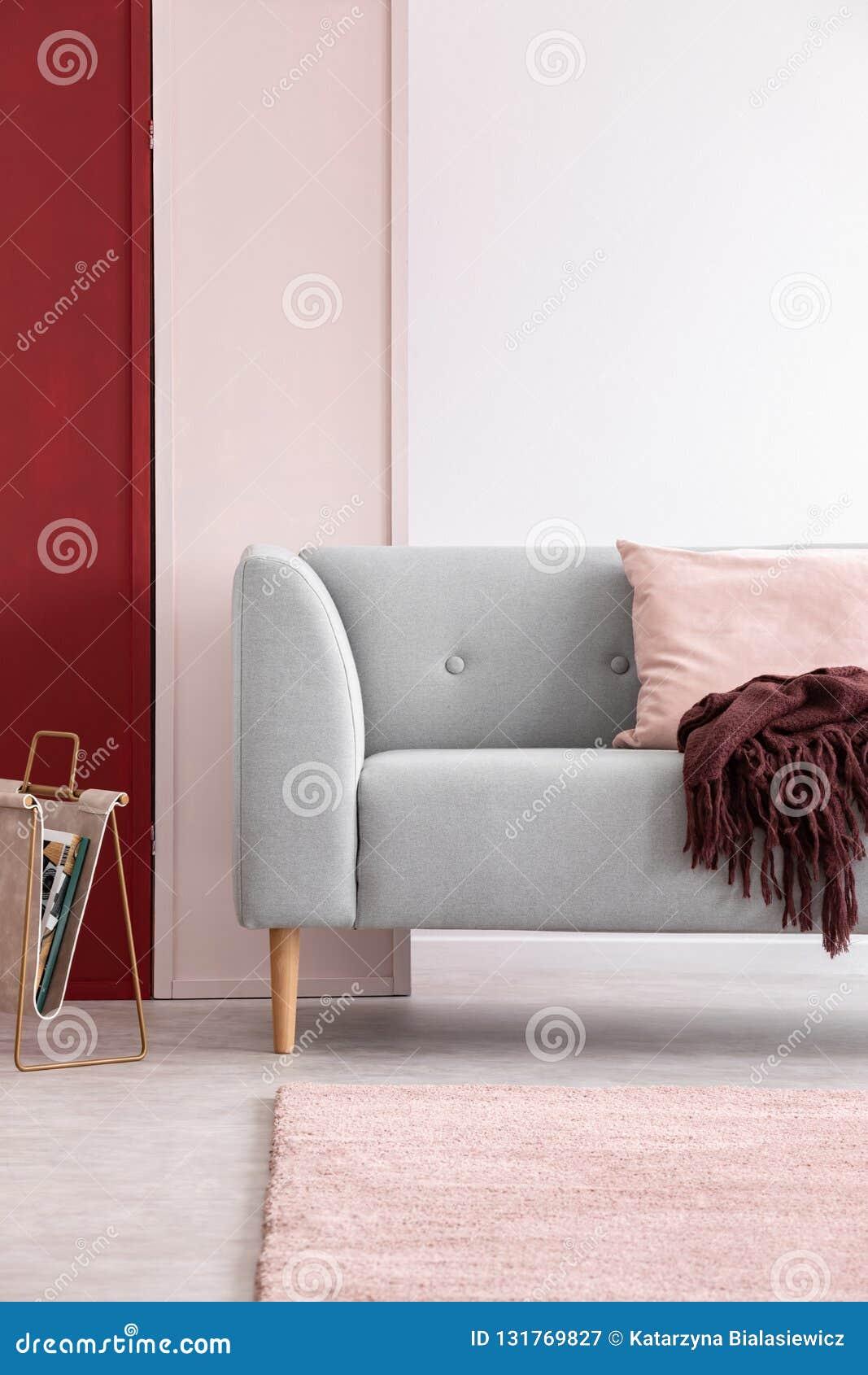Γκρίζος καναπές στο φωτεινό εσωτερικό καθιστικών με τον τρία χρωματισμένο τοίχο, πραγματική φωτογραφία