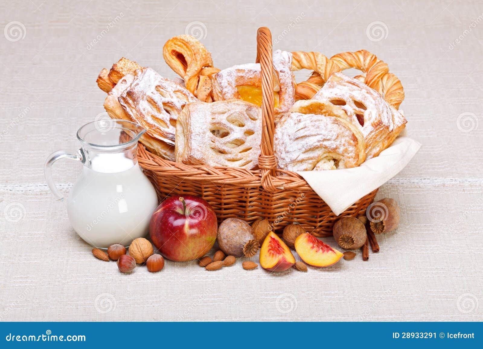 Γλυκά κέικ στη διακόσμηση καλαθιών, καρπού και γάλακτος