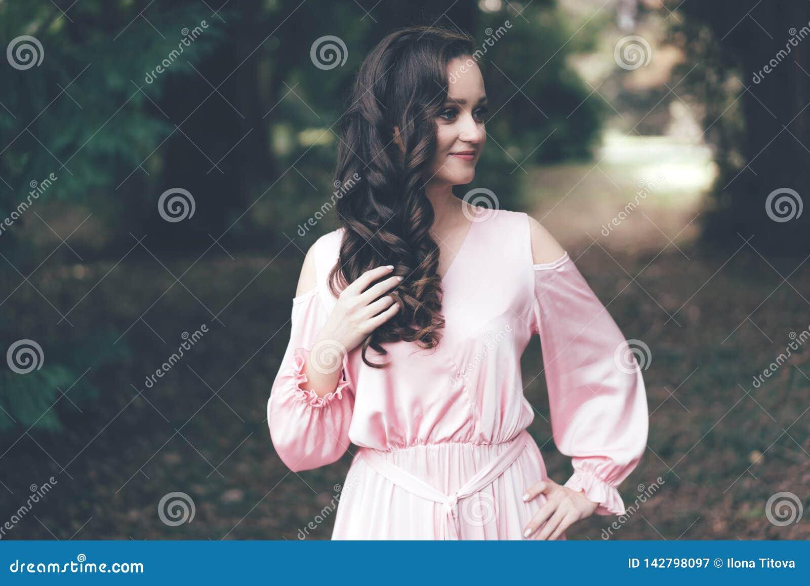 Γλυκό brunette με τις μπούκλες σε ένα φόρεμα