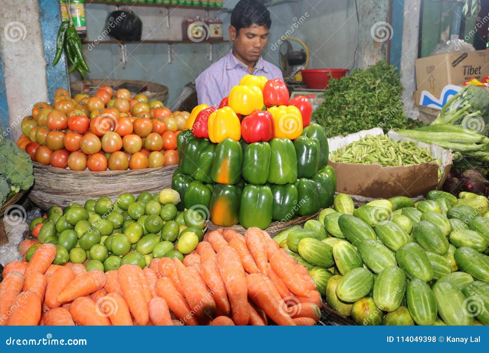 Γλυκό Capciam, κόκκινο πράσινο κίτρινο γλυκό πιπέρι τσίλι στο του Μπαγκλαντές φυτικό κατάστημα με το φύλακα καταστημάτων
