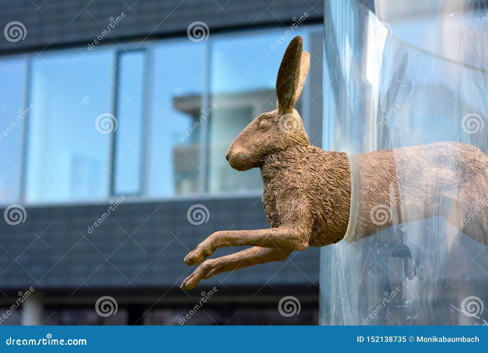 Γλυπτό ενός κουνελιού χαλκού που πηδά μέσω μιας στεφάνης γυαλιού από τον καλλιτέχνη Sabrina Hohmann