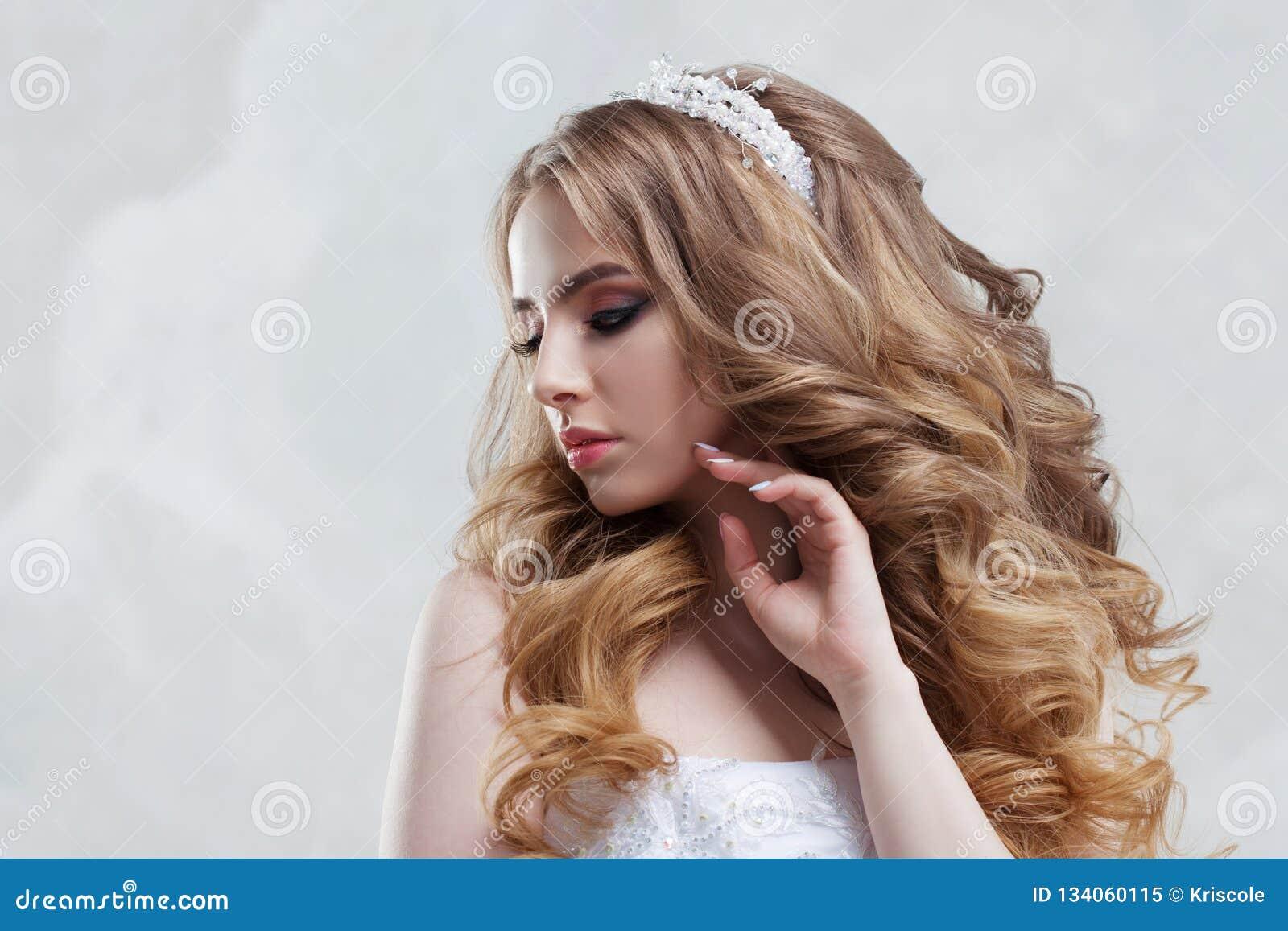 Γοητεία της νέας νύφης με την πολυτέλεια hairstyle όμορφη γαμήλια γυναίκα φορεμάτων Hairstyle με τις χνουδωτές μπούκλες