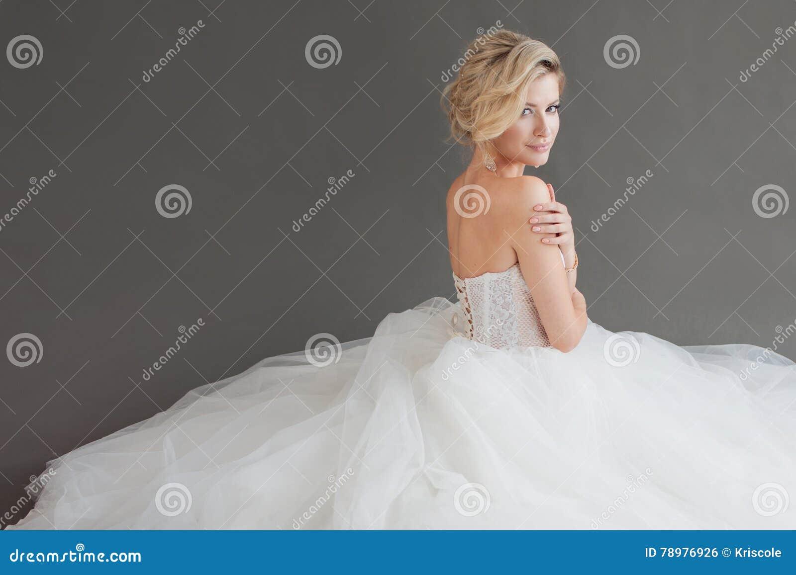 Γοητεία της νέας νύφης στο πολυτελές γαμήλιο φόρεμα κορίτσι αρκετά λευκό Γκρίζα ανασκόπηση μπακαράδων