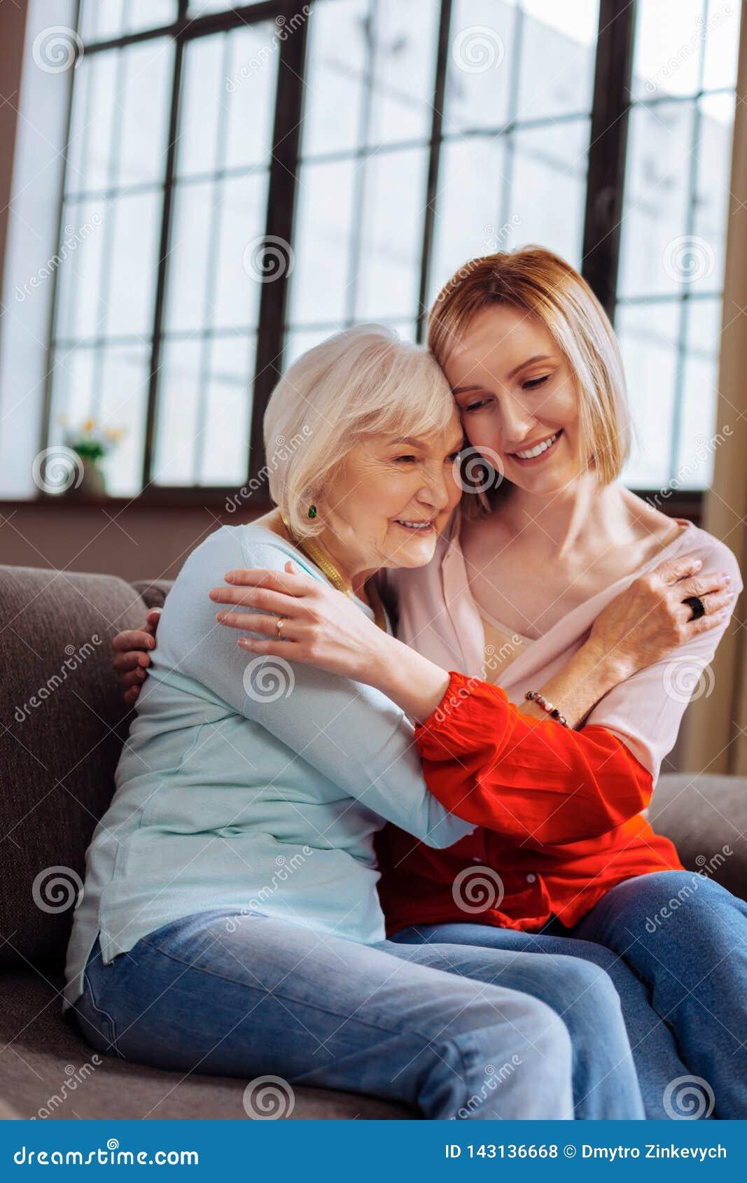 Γοητευτική γυναίκα που αγκαλιάζει με αγάπη την ηλικιωμένη συνεδρίαση κυρίας στον καναπέ