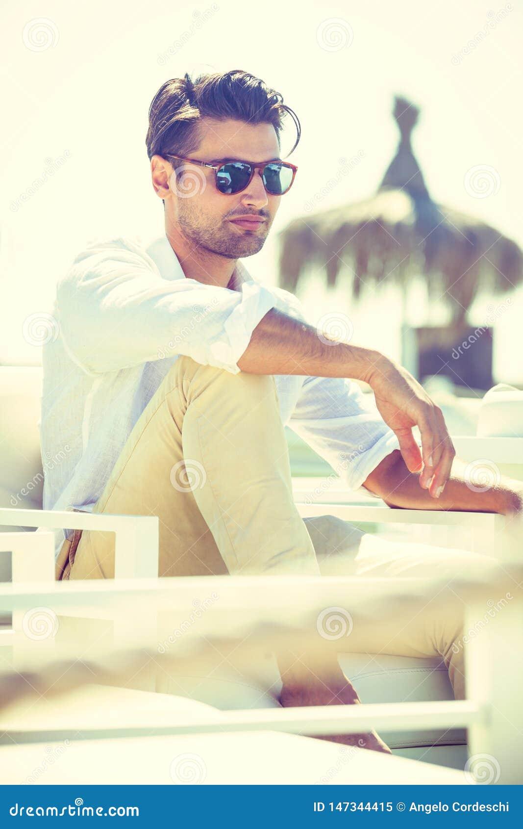Γοητευτικό και ελκυστικό άτομο με τα γυαλιά ηλίου που κάθονται και που χαλαρώνουν σε μια καρέκλα στον ήλιο