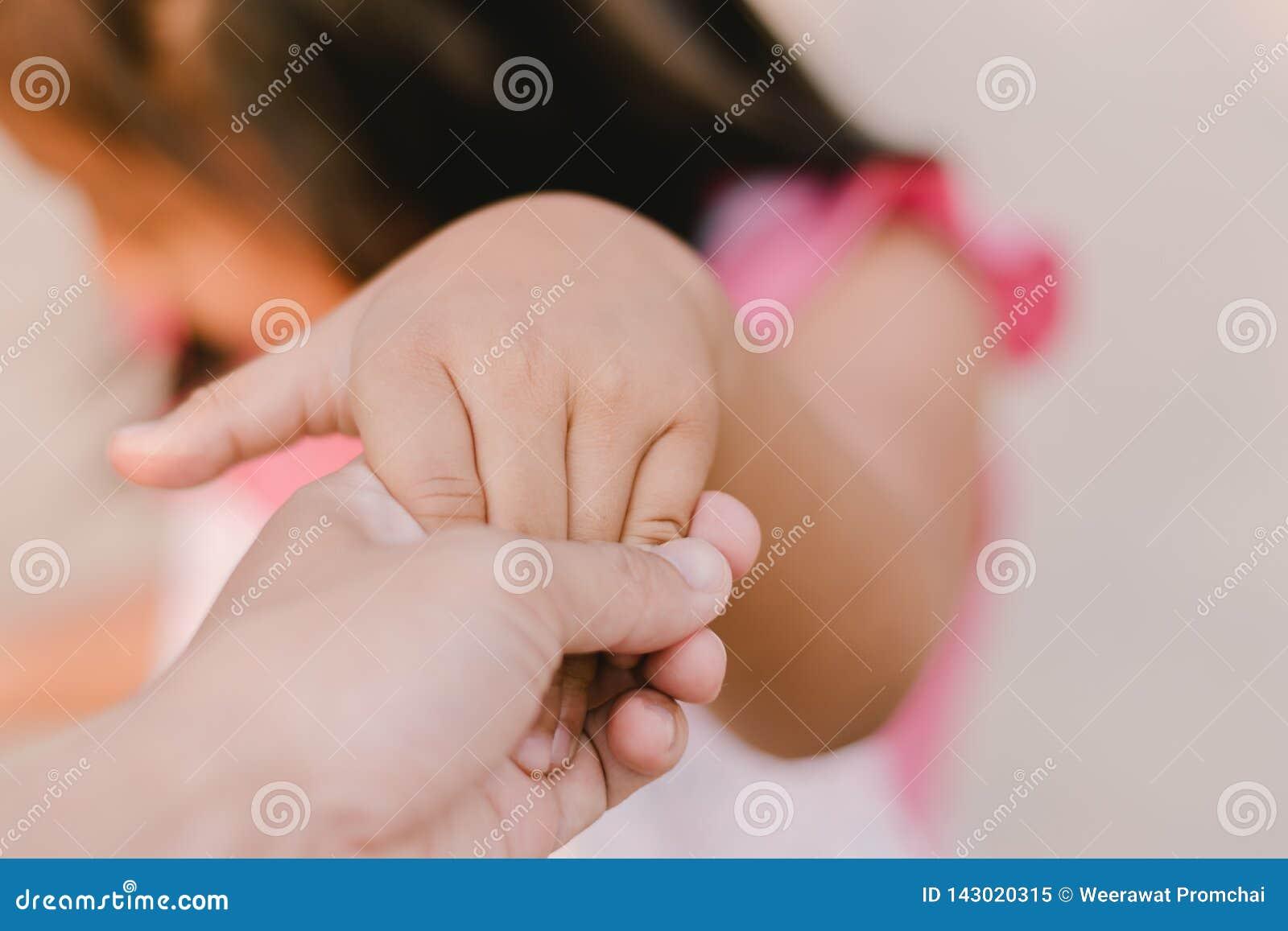 Γονέας που κρατά το χέρι ενός μικρού παιδιού