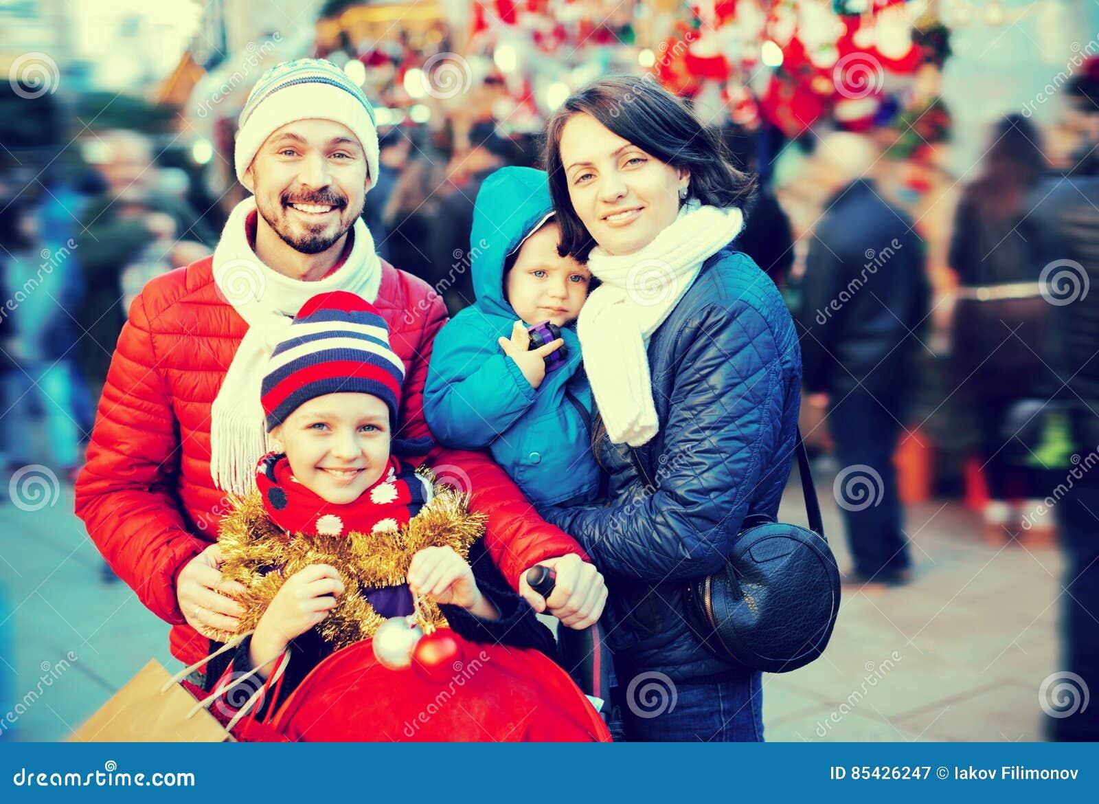 Γονείς με τα παιδιά που επιλέγουν τις διακοσμήσεις Χριστουγέννων στην αγορά