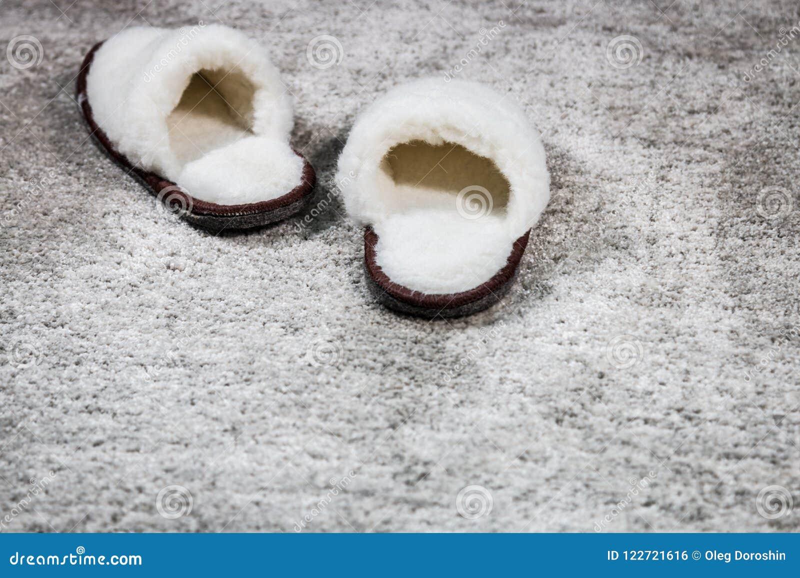 Γούνινο άσπρο χρώμα εγχώριων παντοφλών στον τάπητα