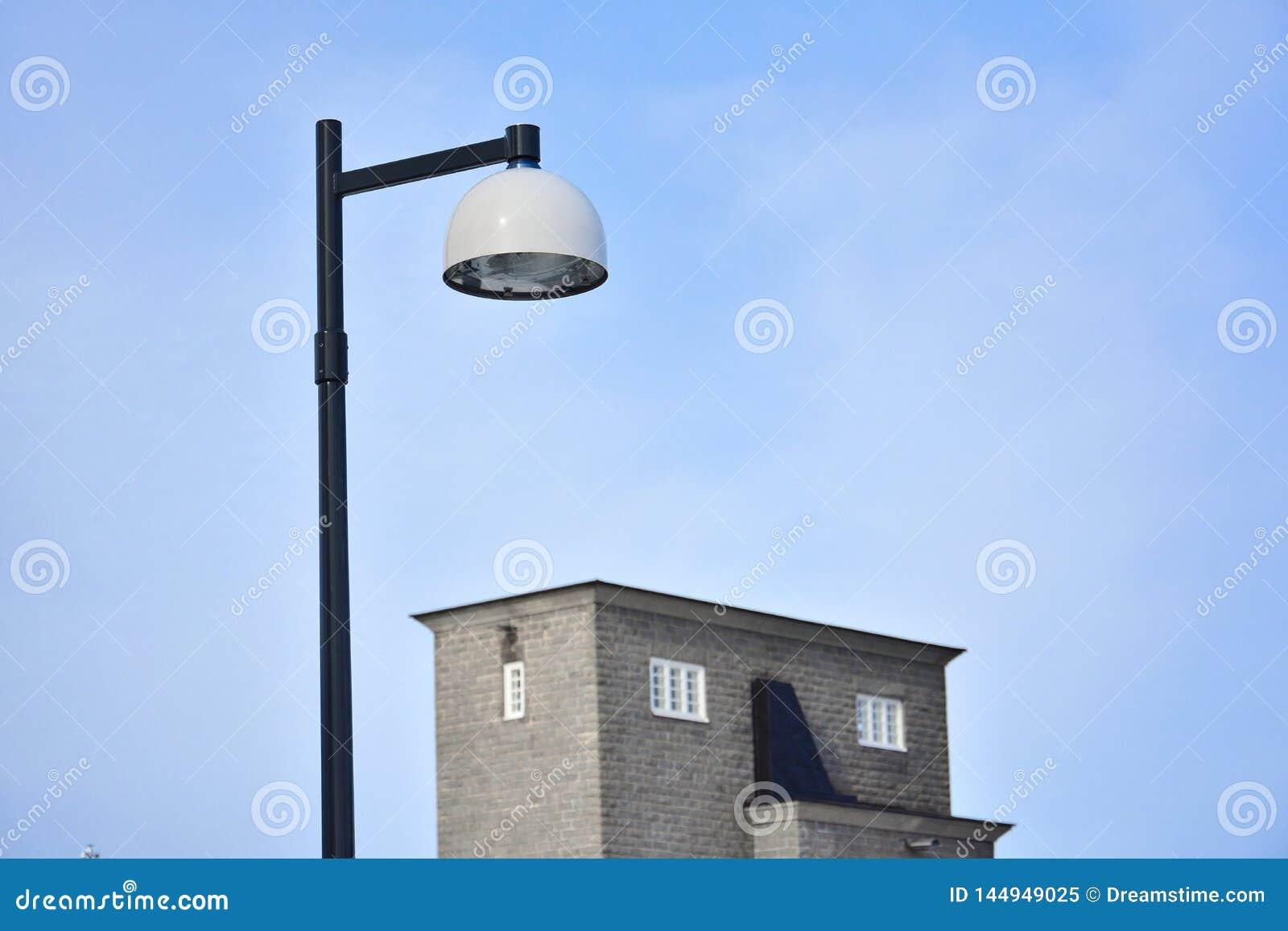 Γραπτός λαμπτήρας μετάλλων και ένα κτήριο στο κλίμα μπλε ουρανού