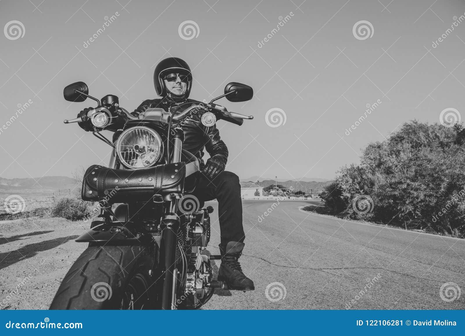 Γραπτό πορτρέτο του ατόμου με το μαύρα κράνος, το σακάκι και τα γυαλιά ηλίου που στέκονται σε μια κλασική αμερικανική μοτοσικλέτα