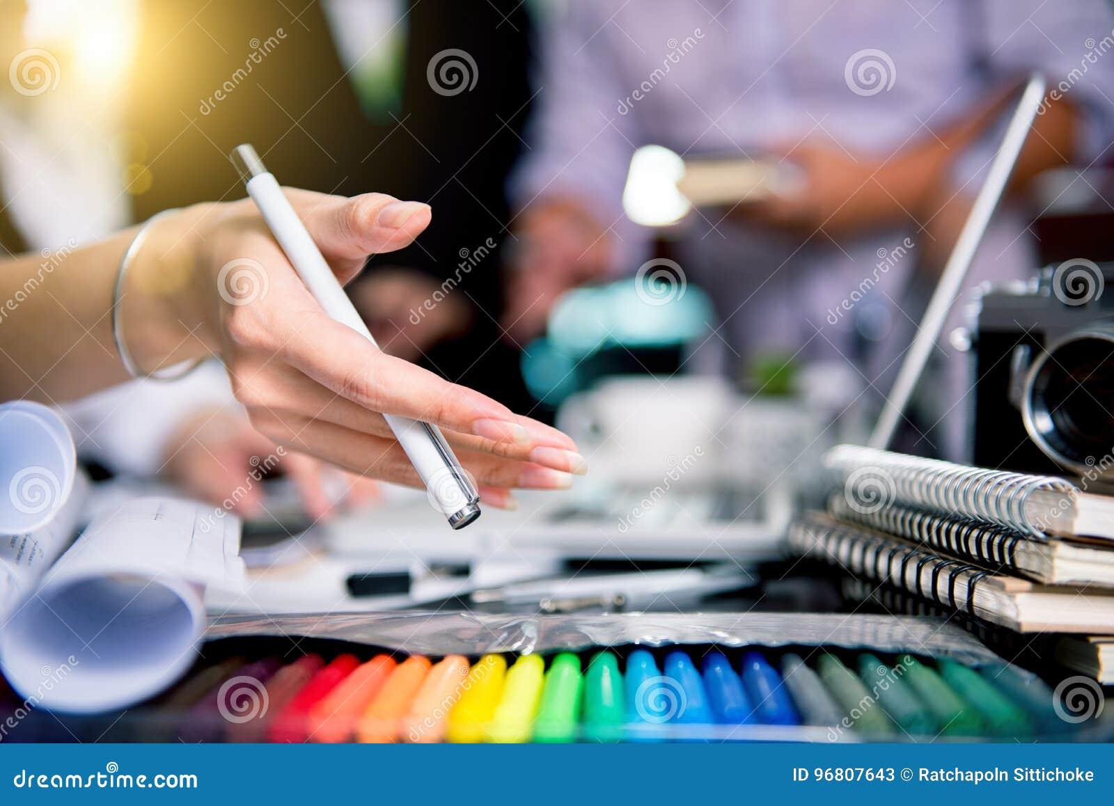 Γραφική ομάδα σχεδιαστών που συναντά τη δημιουργική ταμπλέτα de εργασίας δημιουργικότητας