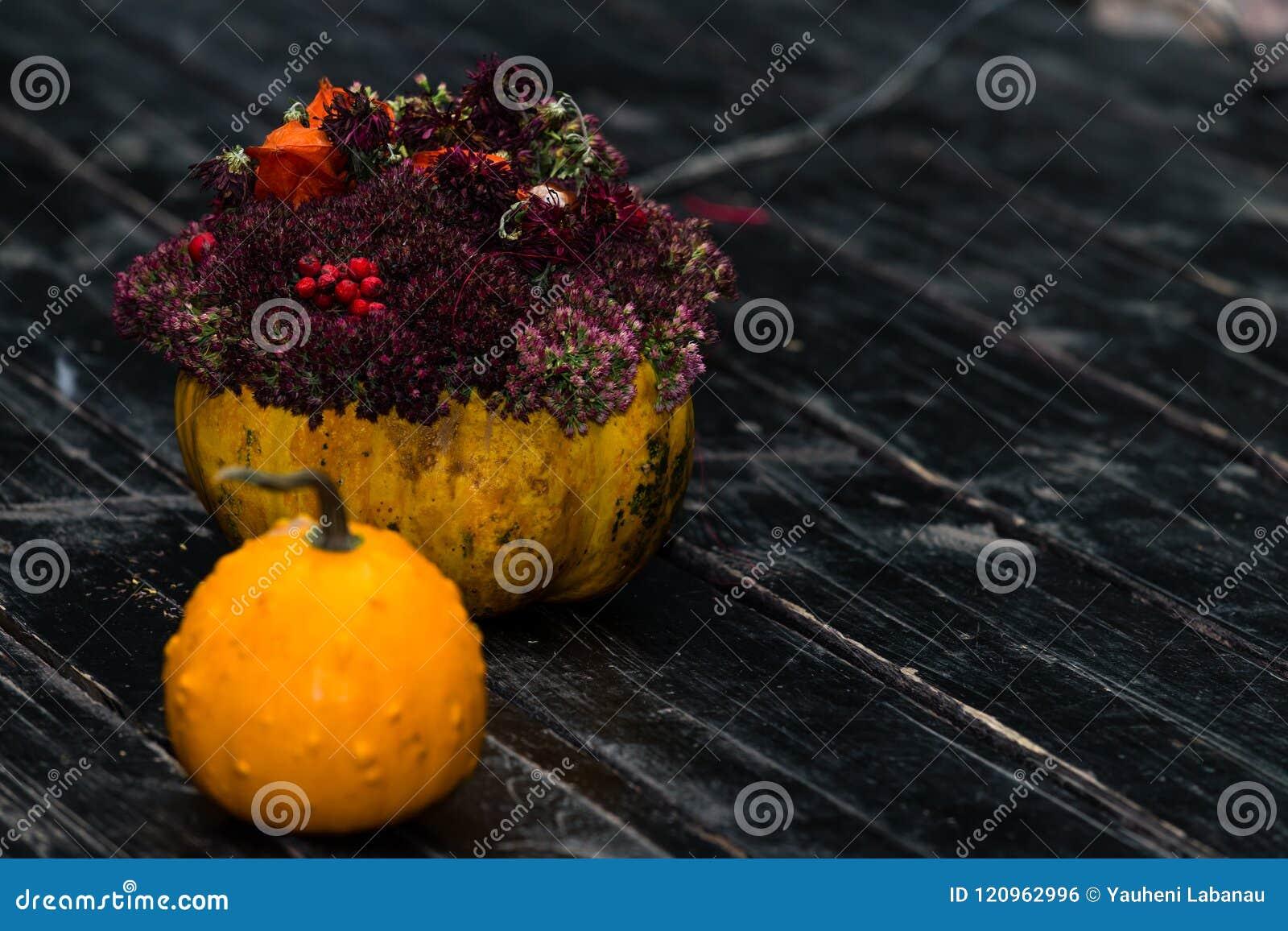 Γρύλος κολοκύθας αποκριών και κολοκύθα με τα λουλούδια στο σκοτεινό ξύλινο β