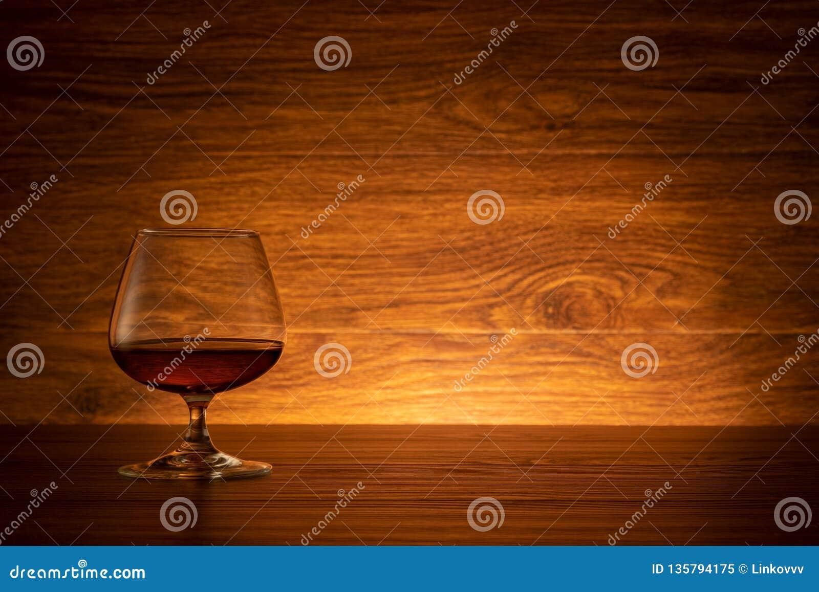 Γυαλί κρασιού κονιάκ στο ξύλινο υπόβαθρο