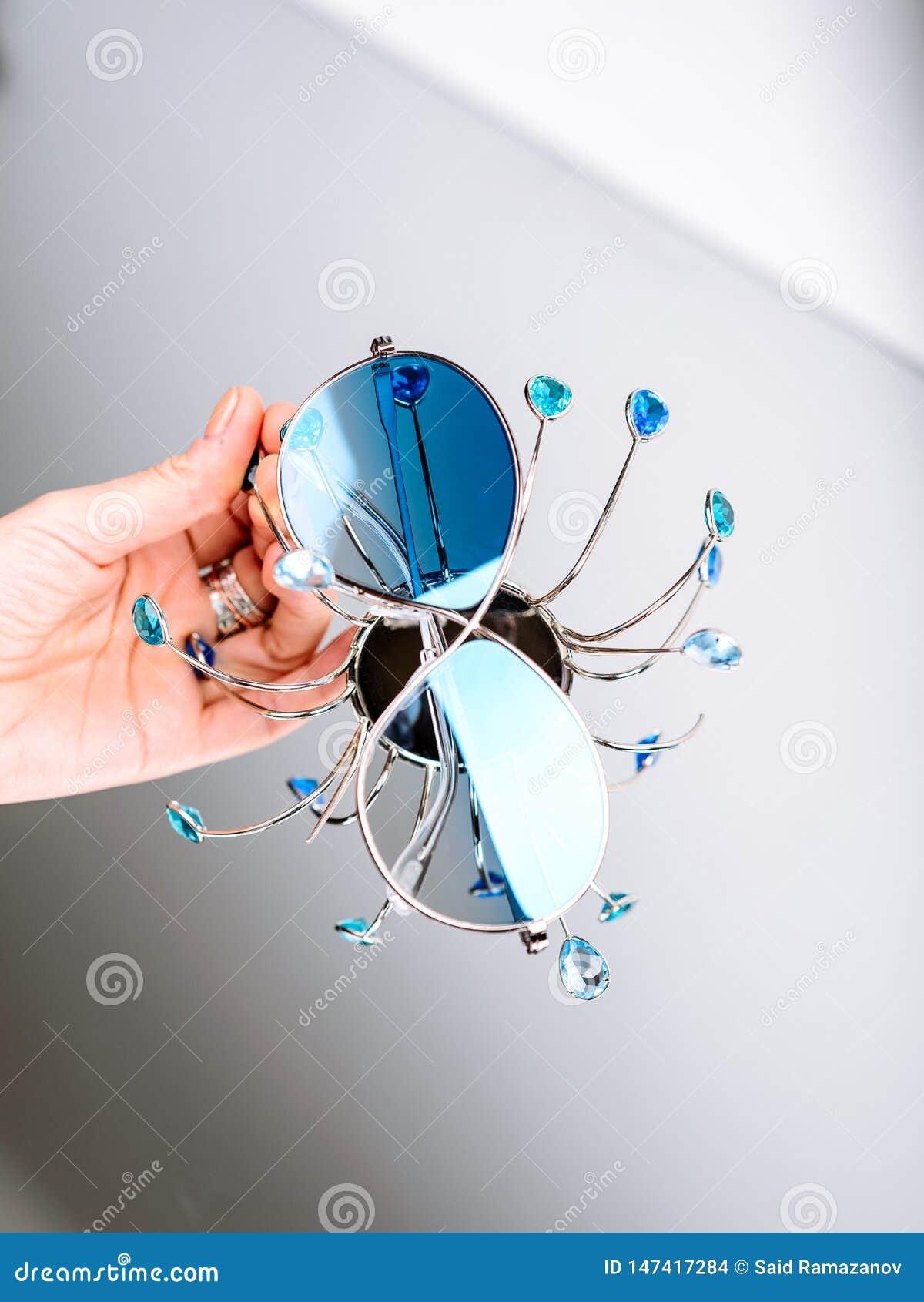 Γυαλιά ηλίου με τα μπλε γυαλιά διαθέσιμα σε ένα γκρίζο υπόβαθρο