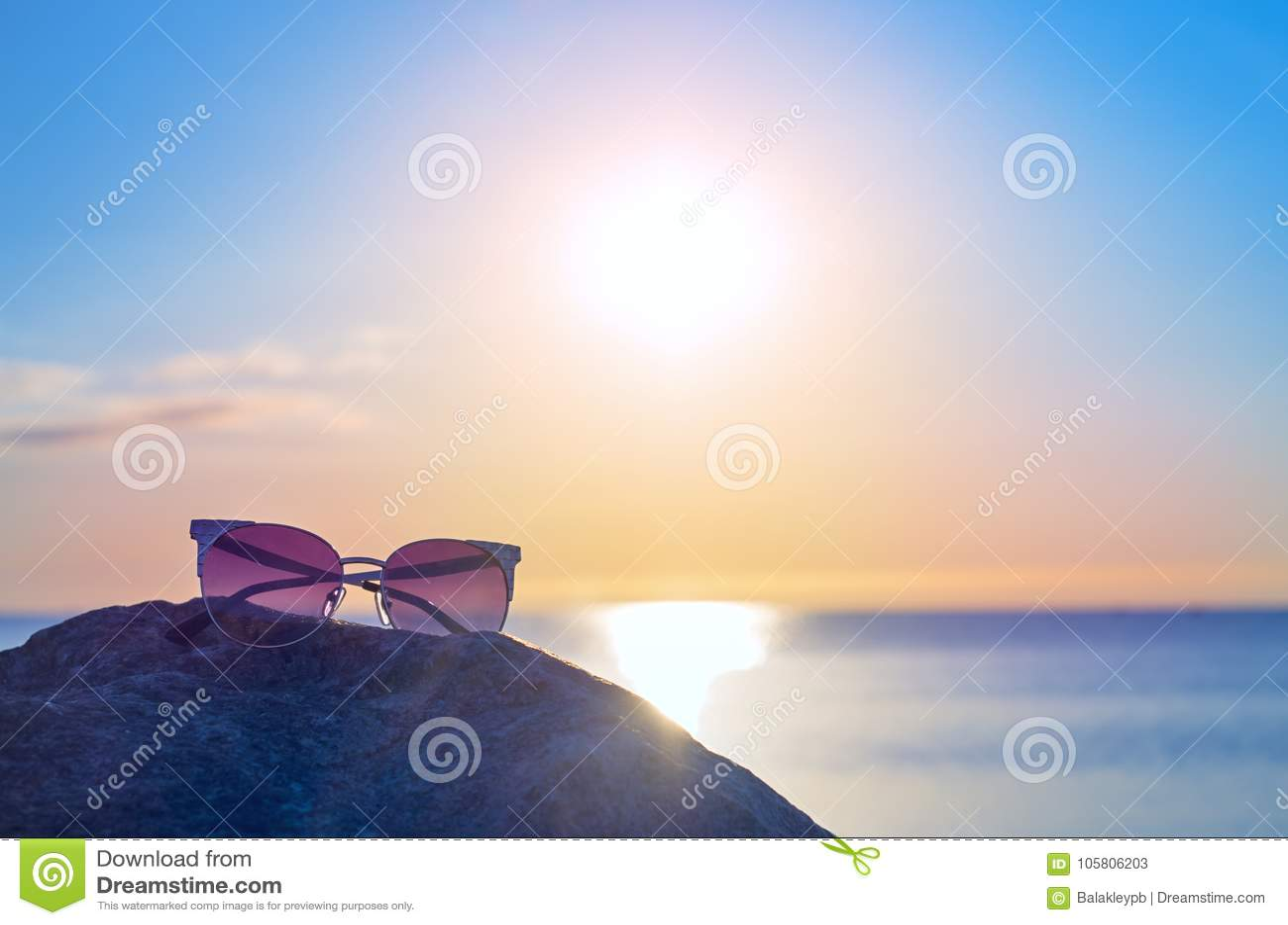 b7dbc67b00 Download Γυαλιά ηλίου σε μια πέτρα κοντά στην ακροθαλασσιά ορίζοντας μπλε  ουρανού ανατολής Στοκ Εικόνα -