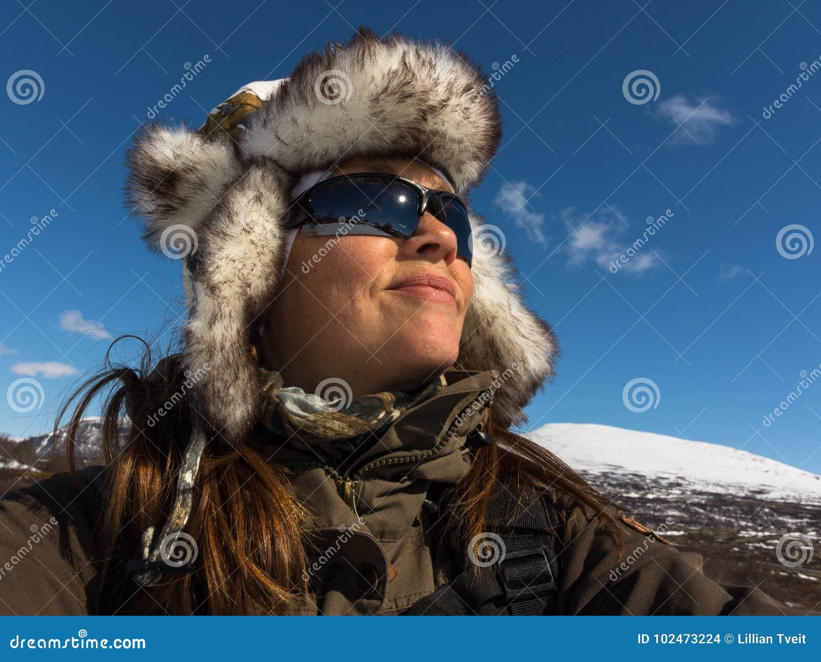 Γυναίκα ευτυχής να είναι στο χειμερινό τοπίο, με το θερμό camo ΚΑΠ και τα γυαλιά ηλίου
