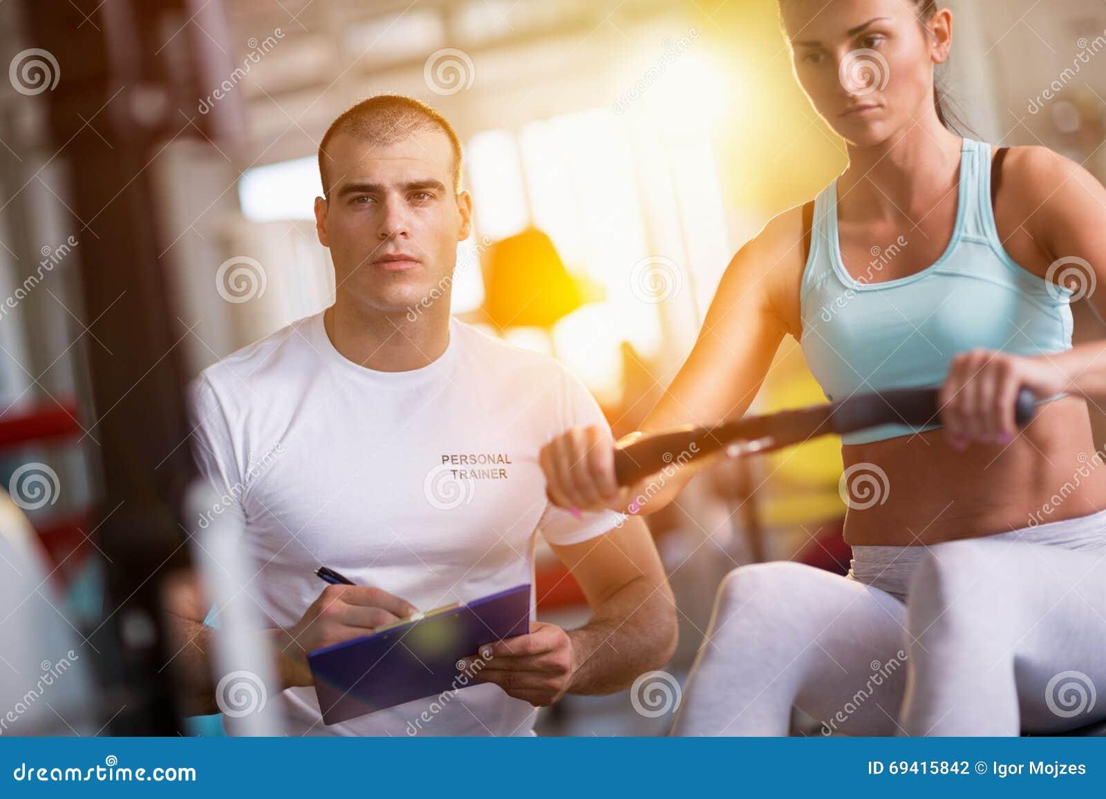Γυναίκα και εκπαιδευτής που επιλύουν στη μηχανή άσκησης στη γυμναστική